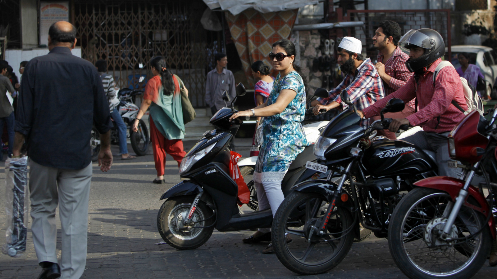A woman riding a scooter waits for a traffic signal along a street in Mumbai February 5, 2014. 'Plush pink' and 'burgundy bliss' scooters are the new buzz on India's roads, even as the rest of the autos market is sputtering amid an economic slowdown. Young, well-heeled and independent-minded women, who are also conscious of the perils of using public transport, are helping to propel a boom in sales of scooters.