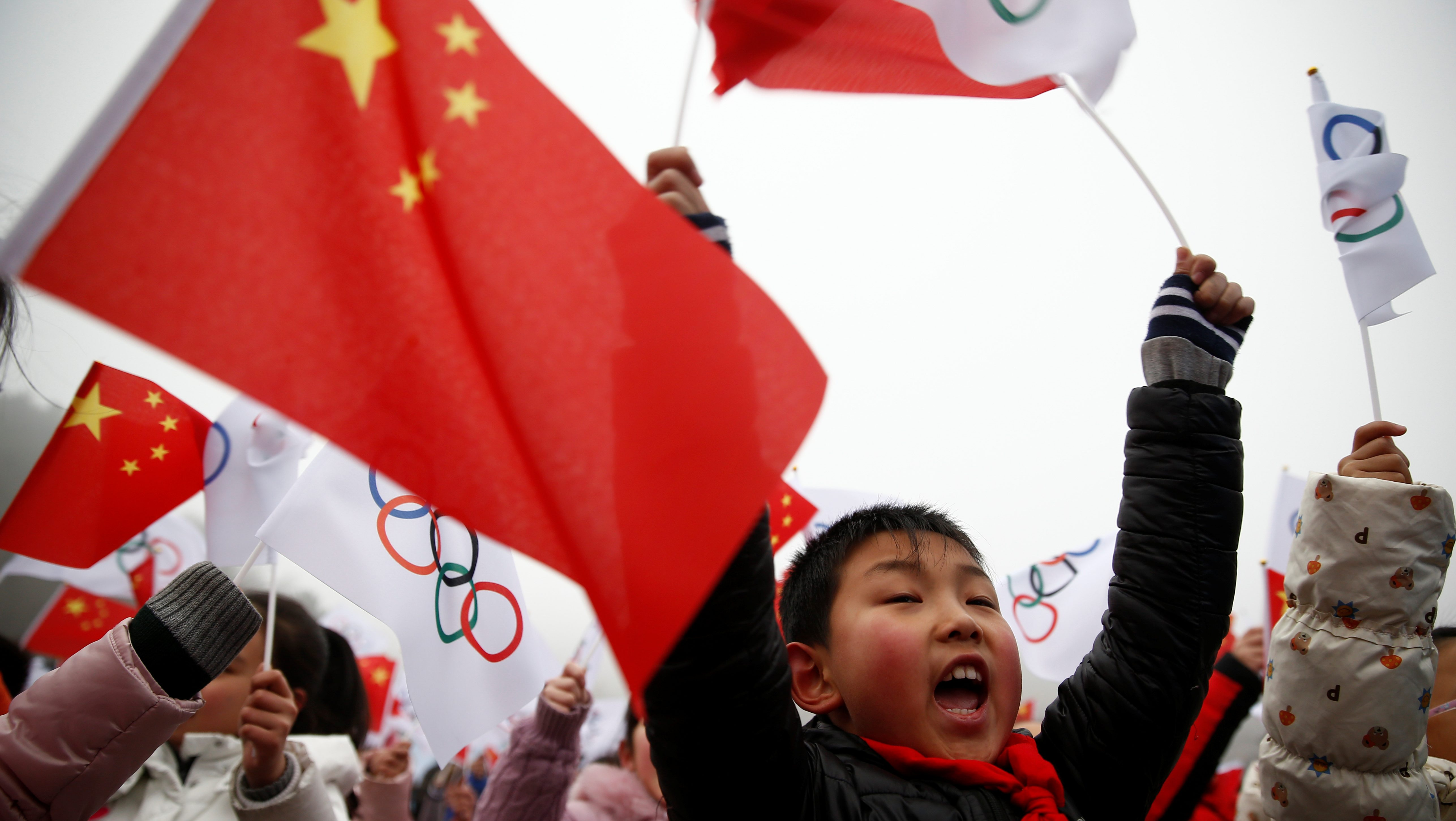 Children wave Chinese and Olympic flags during a ceremony marking the start of the tour of the Olympic flag leading up to the Beijing 2022 Olympic and Paralympic Winter Games at the Badaling section of the Great Wall in Yanqing district in Beijing, China, February 27, 2018.