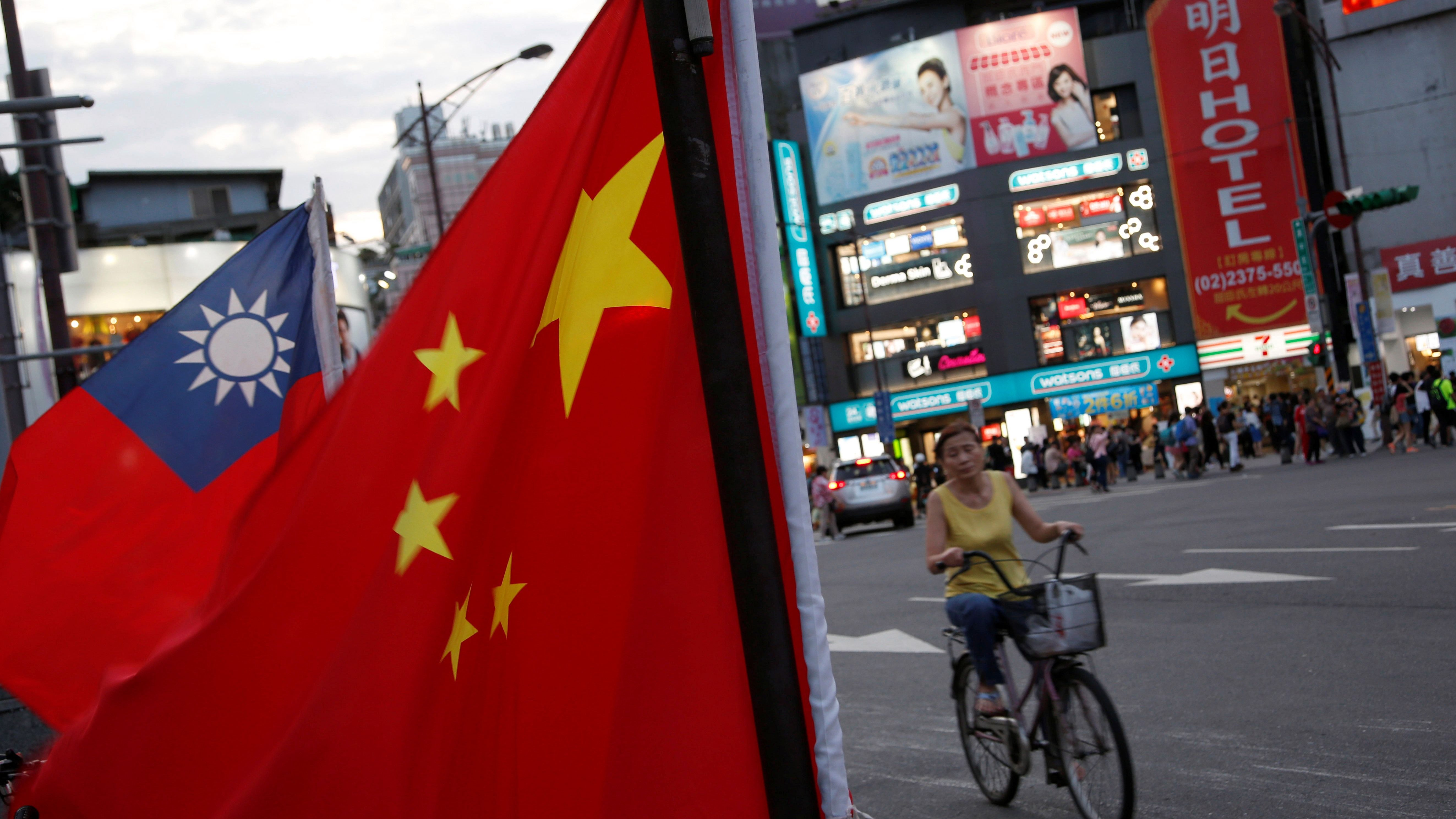 A woman rides a bike past Taiwan and China national flags during a rally held by a group of pro-China supporters calling peaceful reunification, 6 days before  the inauguration ceremony of President-elect Tsai Ing-wen, in Taipei, Taiwan May 14, 2016.