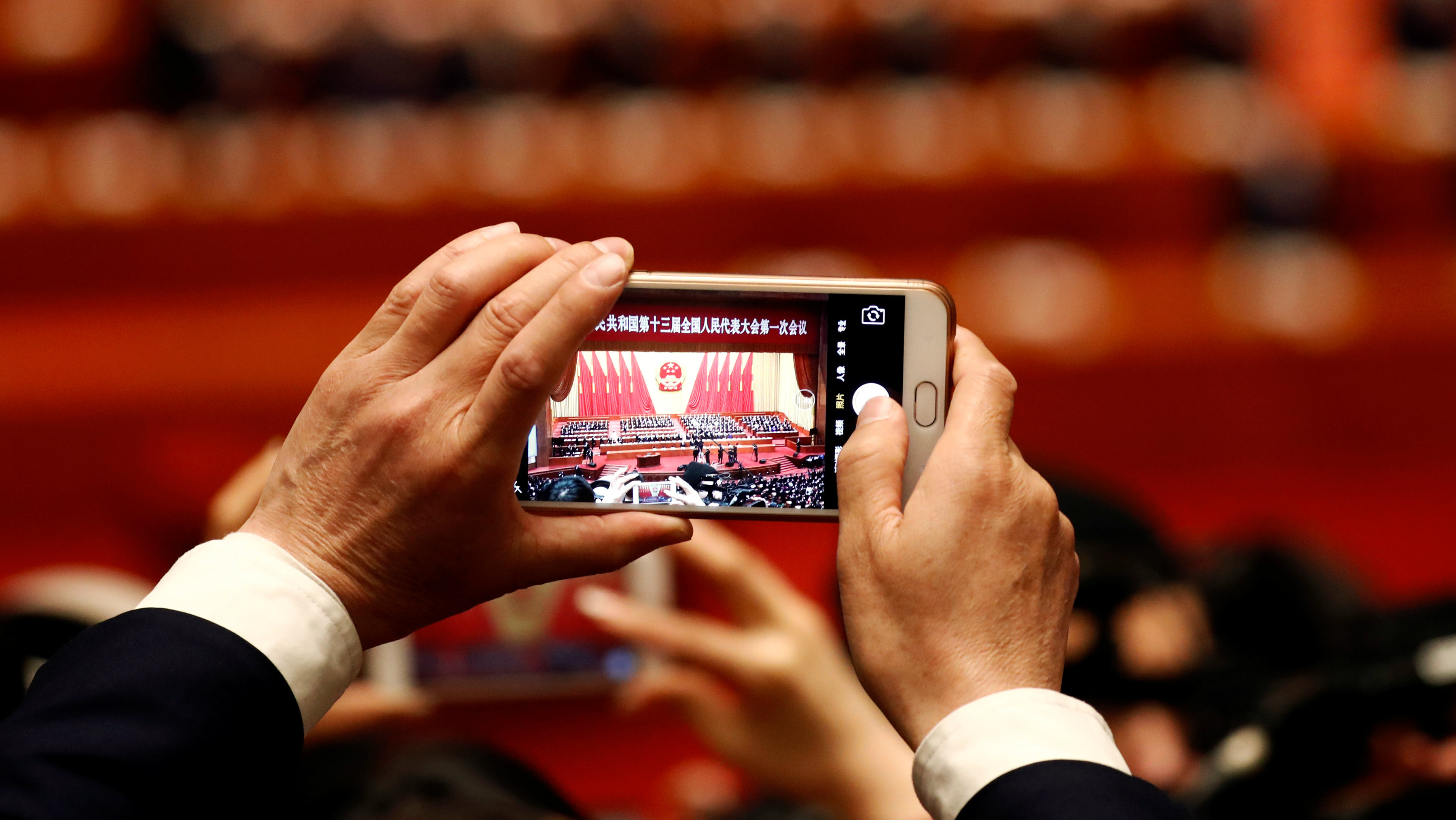 A man takes picture of military delegates arriving for the opening session of the National People's Congress (NPC) at the Great Hall of the People in Beijing, China March 5, 2018.