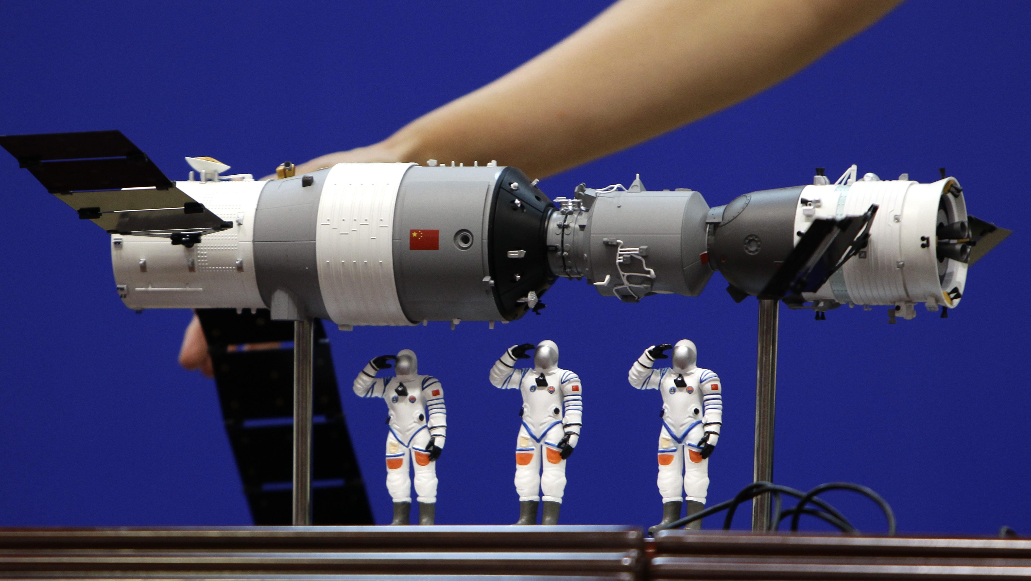 A model of the Shenzhou-9 manned spacecraft ( R) docking with the orbiting Tiangong-1 space lab module (L) and three Chinese astronauts is displayed during a news conference at Jiuquan Satellite Launch Center, in northwest China's Gansu province, June 15, 2012. The Shenzhou-9 manned spacecraft will be launched at 18:37 (10:37 GMT) on June 16, 2012, according to a decision made by China's manned space docking program headquarters, Xinhua News Agency reported.