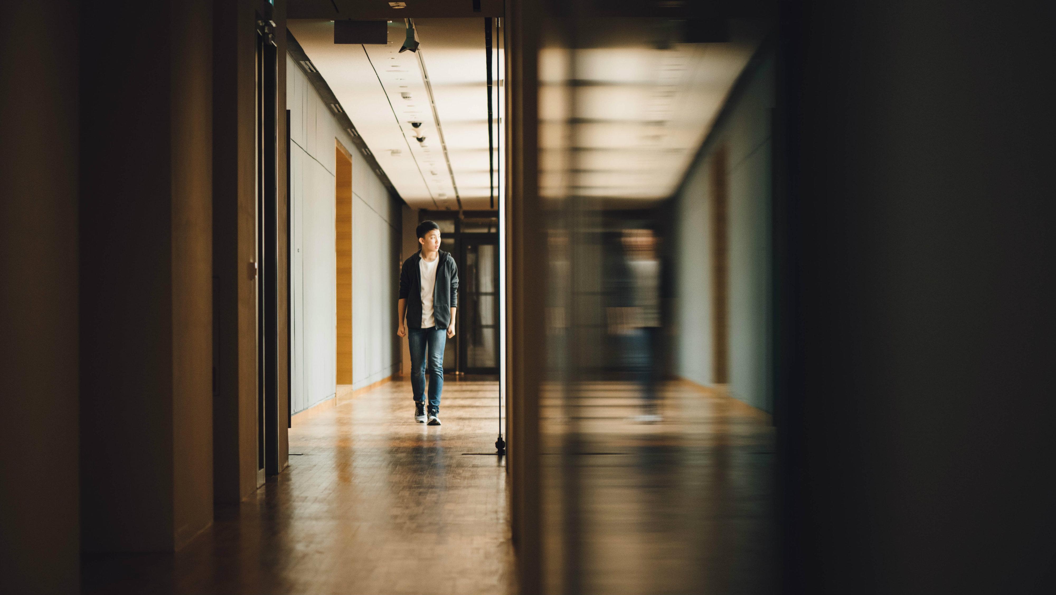 Teen walking in school hall.