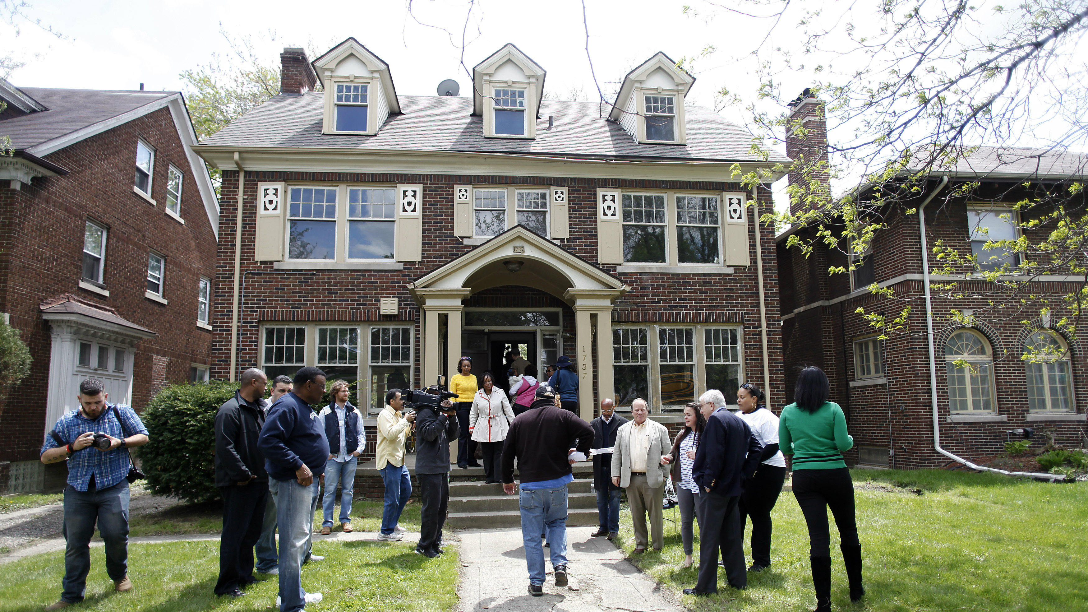 People enter and exit a home being auctioned in the Boston Edison neighborhood of Detroit