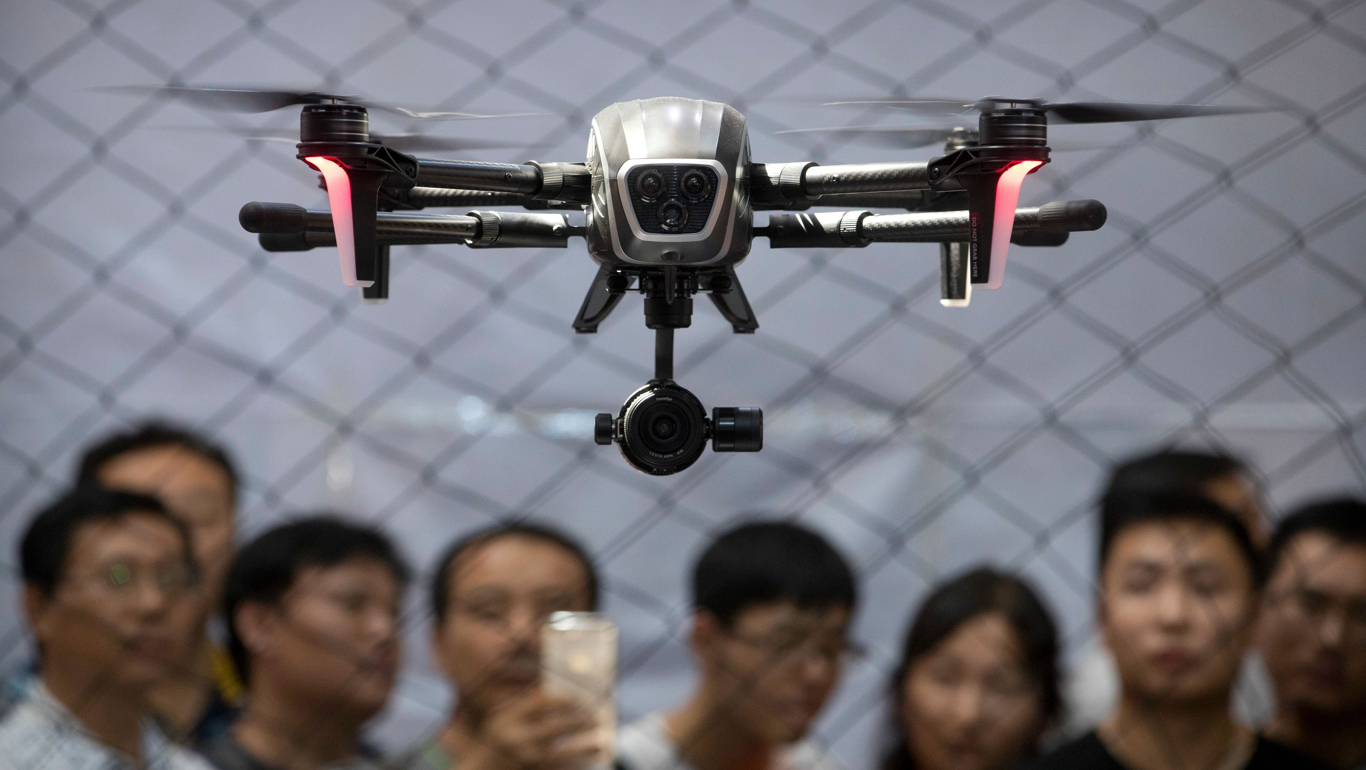 Visitors watch as a drone made by PowerVision hovers during a demonstration at the World Robot Conference in Beijing, Thursday, Aug. 24, 2017. The annual conference is a showcase of China's burgeoning robot industry ranging from companion robots to those deployed on manufacturing assembly line and entertainment. (AP Photo/Mark Schiefelbein)