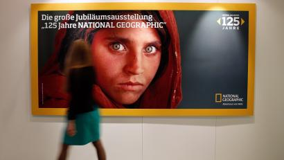 A woman walks by a poster advertising the exhibition '125 Jahre National Geographic' (lit.: 125 Years National Geographic) at the Gruner und Jahr publishing house in Hamburg, Germany, 12 September 2013. National Geographic Germany presents a selection of photographs from the 125 year history of the magazine from 14 September to 13 October.