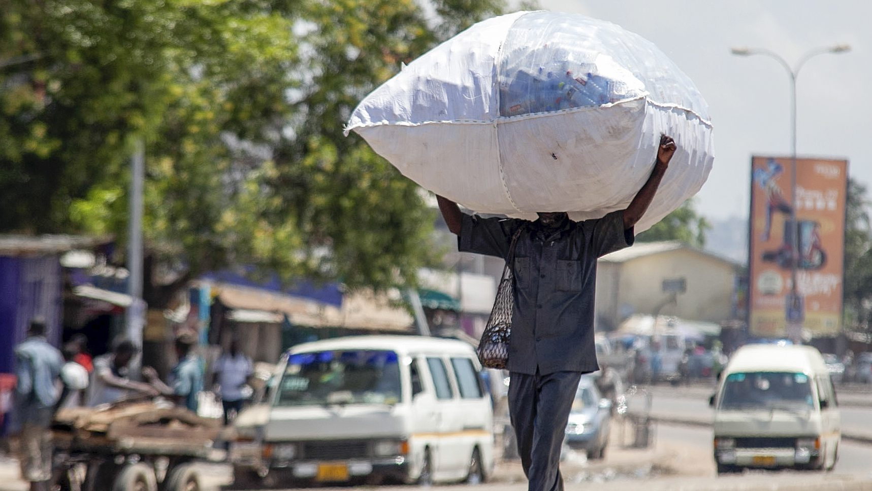 A Ghanaian man walks down a street carrying recyclable plastic bottles in Accra, Ghana.