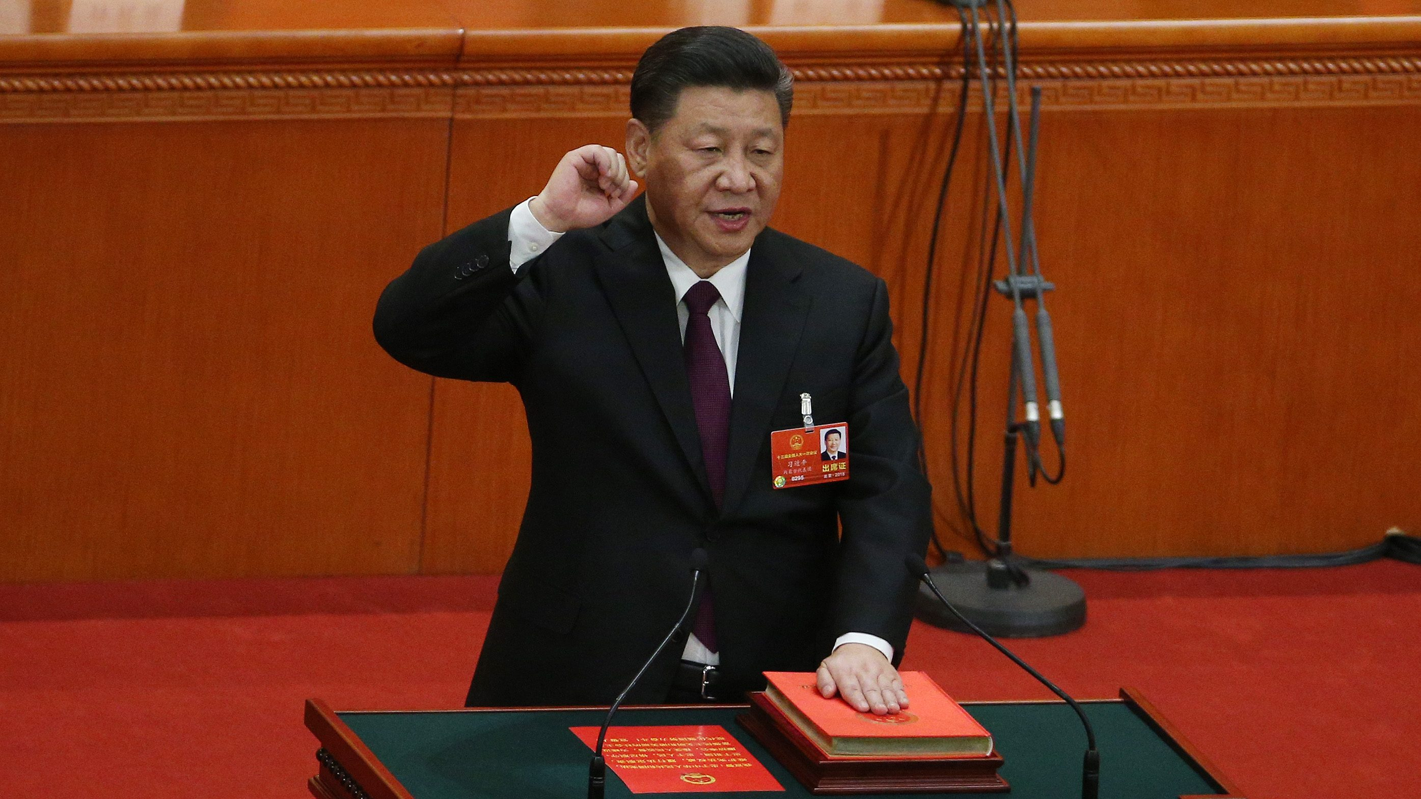 Chinese President Xi Jinping with his hand on the Constitution swears after he is voted as the president for a second term at the fifth plenary session of the first session of the 13th National People's Congress (NPC) at the Great Hall of the People in Beijing, China, 17 March 2018. The NPC has over 3,000 delegates and is the world's largest parliament or legislative assembly though its function is largely as a formal seal of approval for the policies fixed by the leaders of the Chinese Communist Party. The NPC runs alongside the annual plenary meetings of the Chinese People's Political Consultative Conference (CPPCC), together known as 'Lianghui' or 'Two Meetings'.