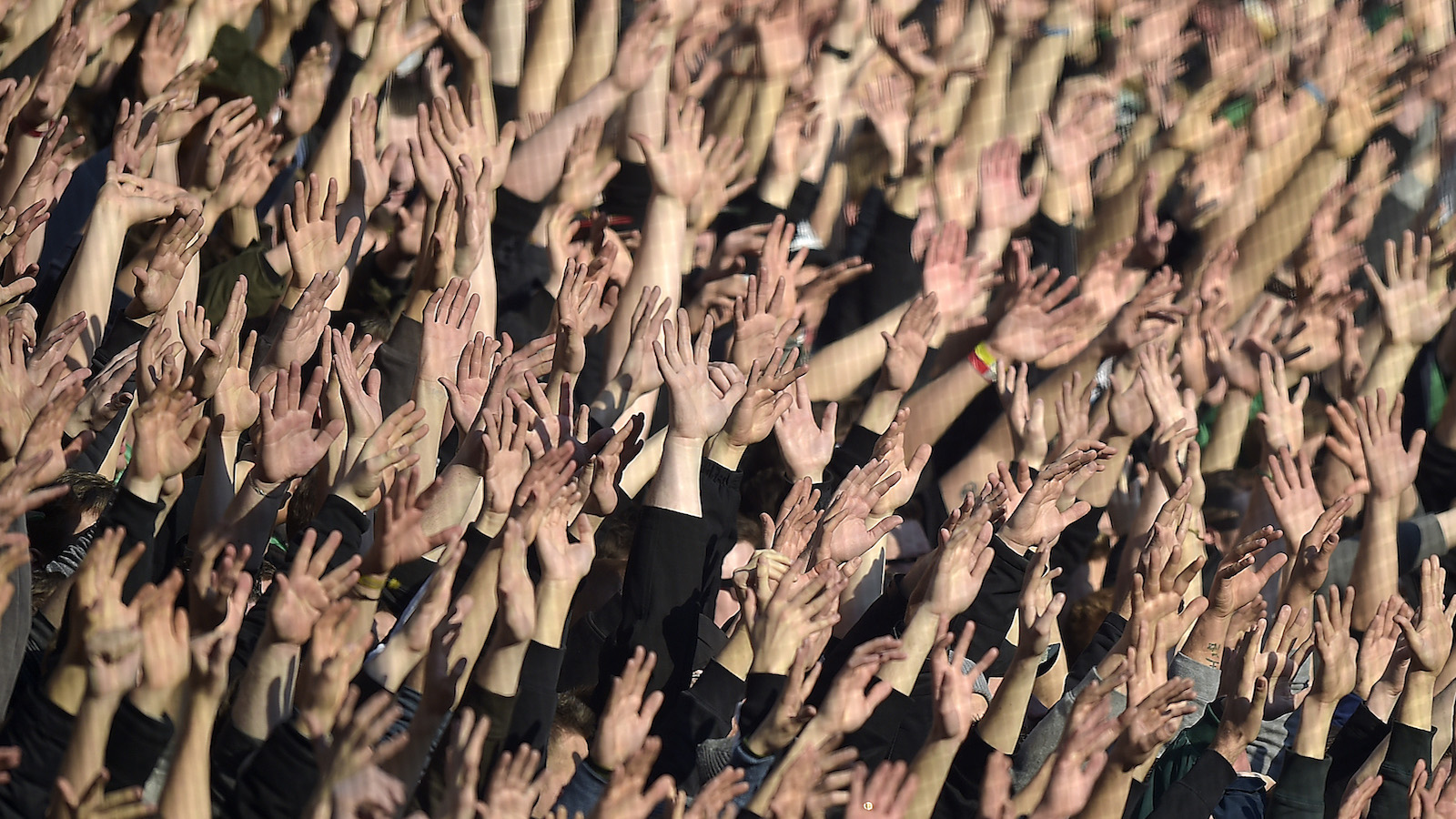 Borussia's supporters holding their hands up during the German Bundesliga soccer match between Borussia Moenchengladbach and 1. FC Cologne in Moenchengladbach, Germany, Saturday, Feb. 14, 2015. (AP Photo/Martin Meissner)