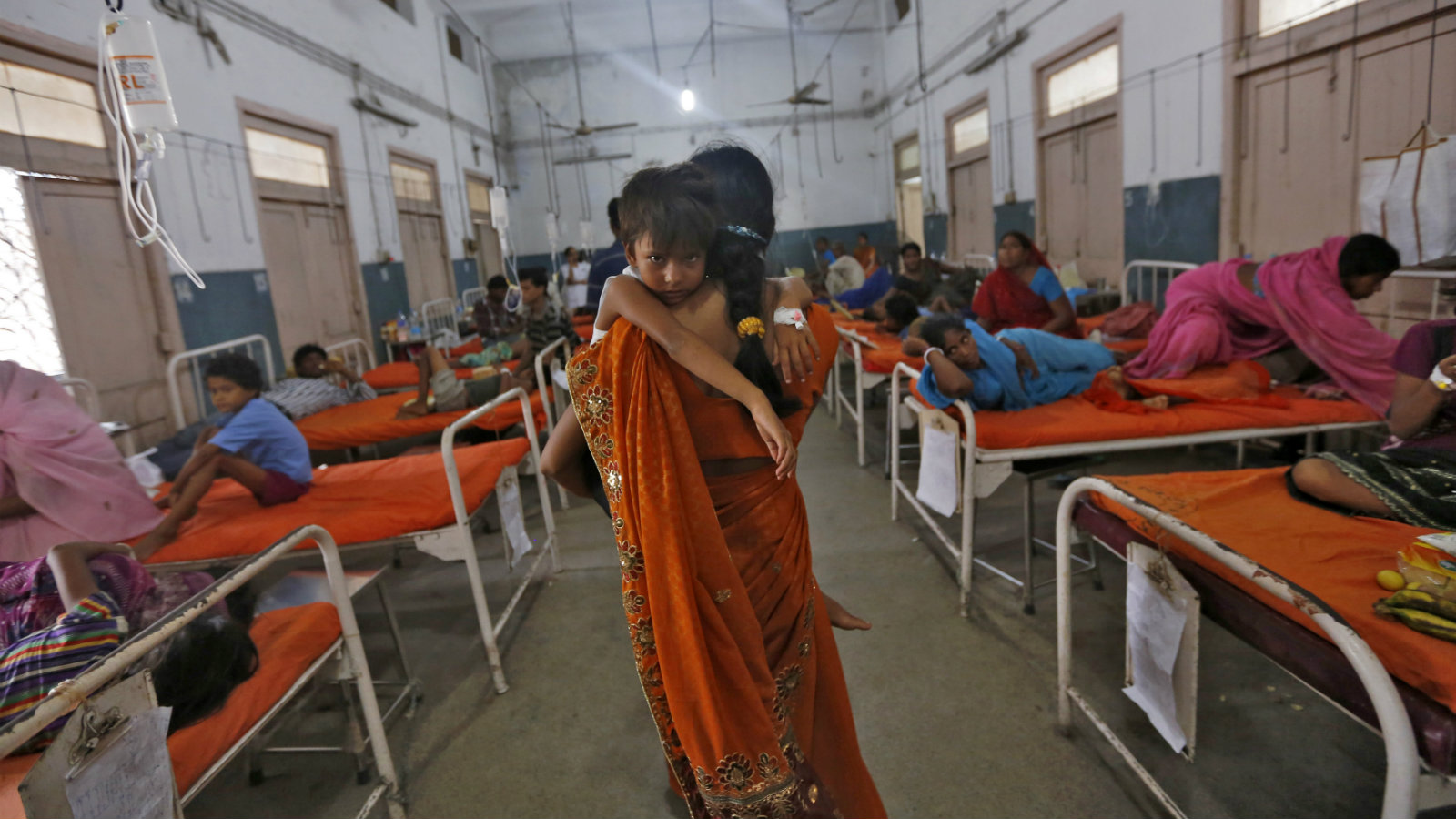 A woman carries her niece who got sick after consuming contaminated meals given to children at a school on Tuesday, in the eastern Indian city of Patna July 18, 2013. The Indian government announced on Thursday it would set up an inquiry into the quality of food given to school pupils in a nationwide free meal scheme after at least 23 children died in one of the deadliest outbreaks of mass poisoning in years.
