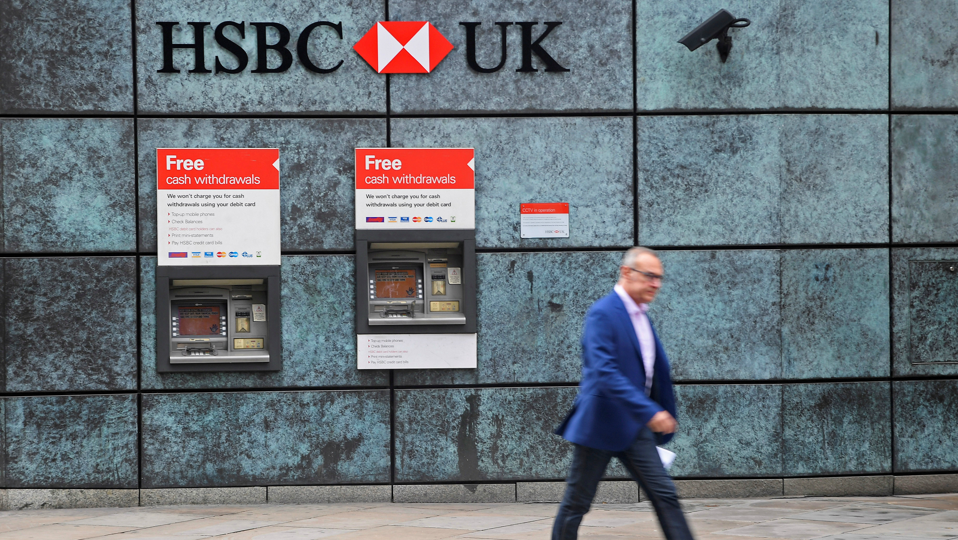 A worker walks past a branch of HSBC bank in the City of London financial district
