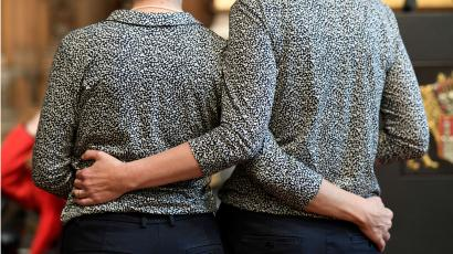 A same sex couple in matching outfits hugging each other.