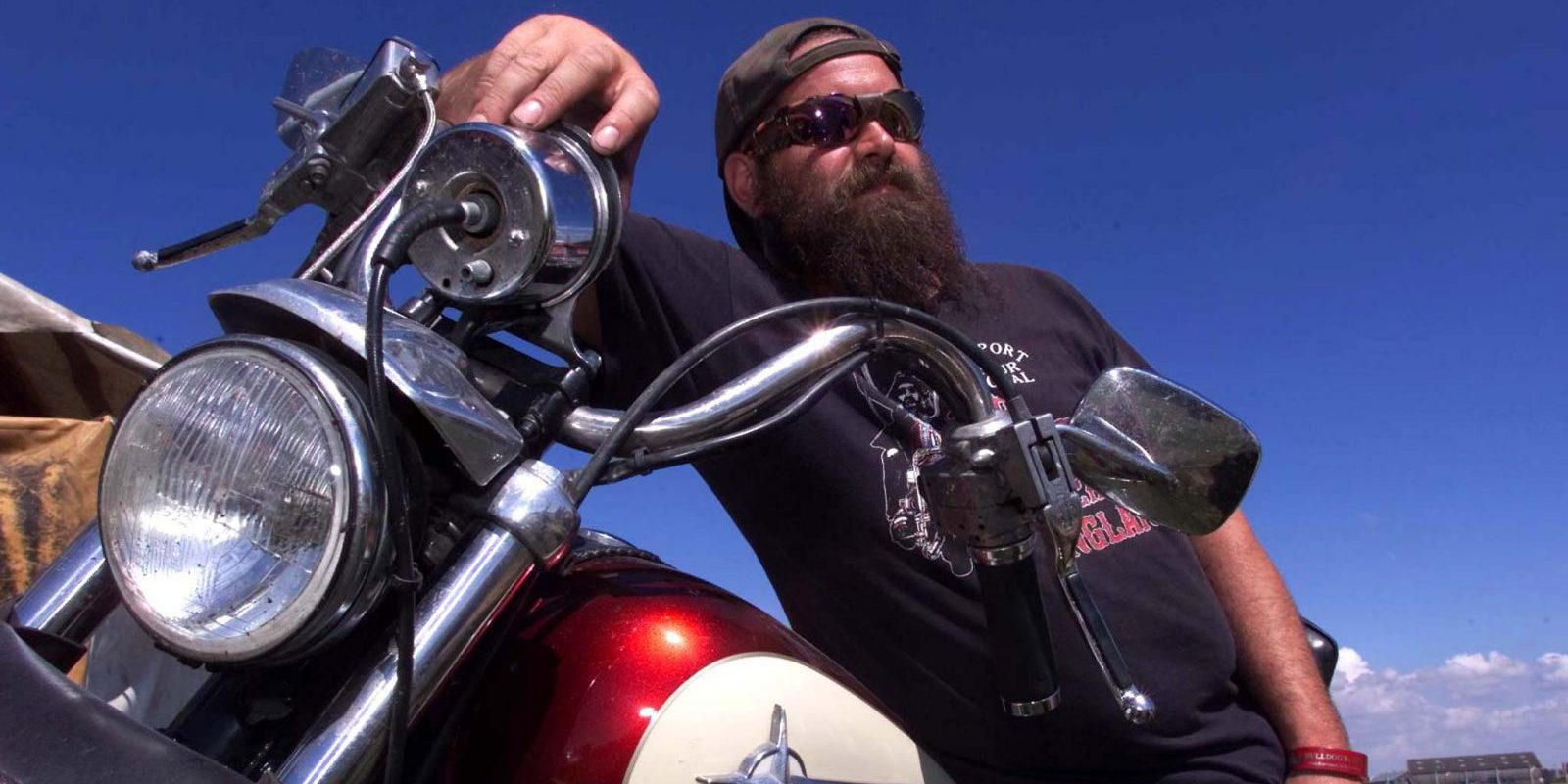 A Hells Angel biker leans on his Harley Davidson at The Bulldog Bash at Long Marston airfield in Warwickshire August 5.