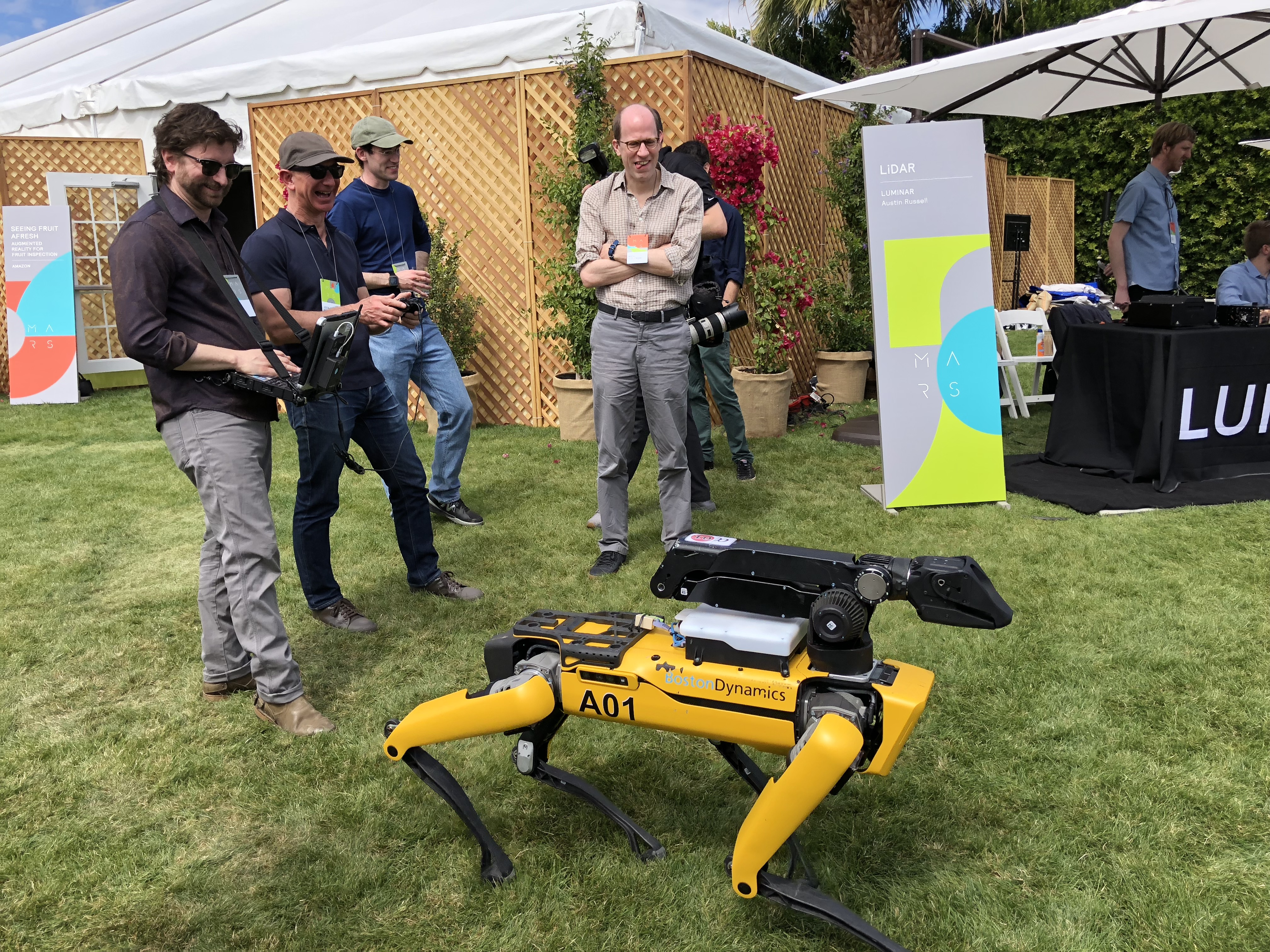 Jeff Bezos, center, pilots the Boston Dynamics SpotMini.