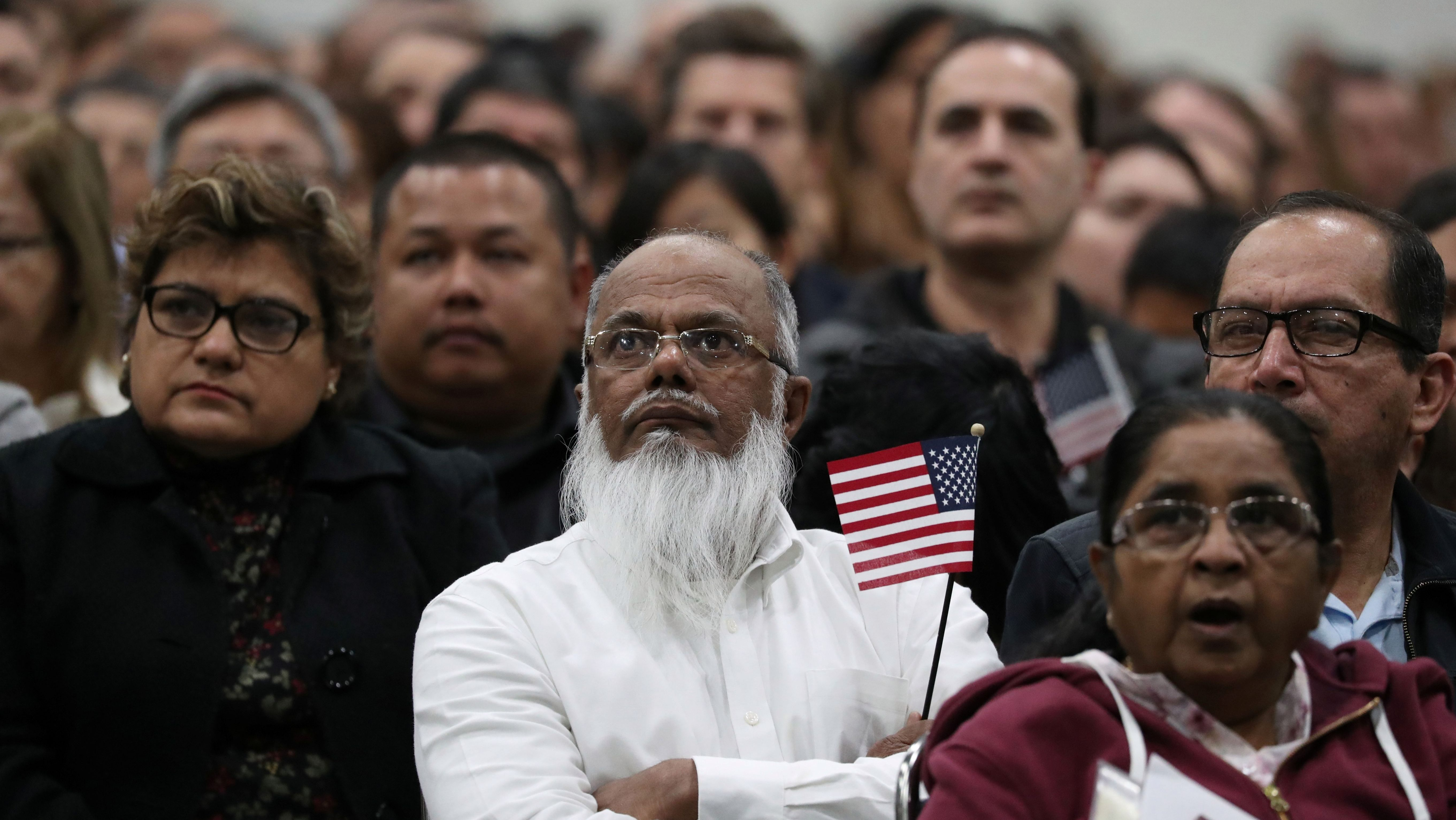 Immigrants participate in a naturalization ceremony to become new U.S. citizens