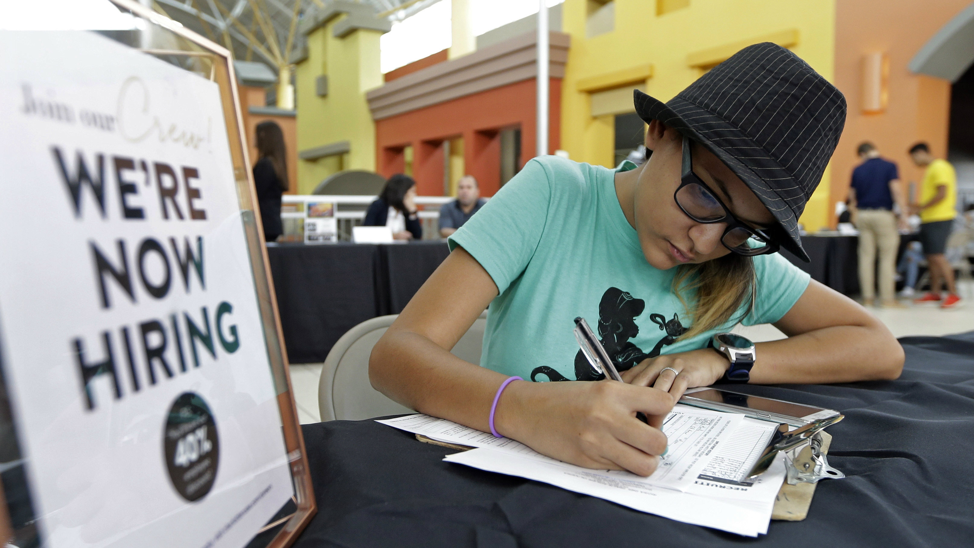 Job seeker Alejandra Bastidas fills out an application at a job fair, Tuesday, Oct. 3, 2017, at Dolphin Mall in Sweetwater, Fla. On Wednesday, Oct. 4, 2017, payroll processor ADP reports how many jobs private employers added in September.