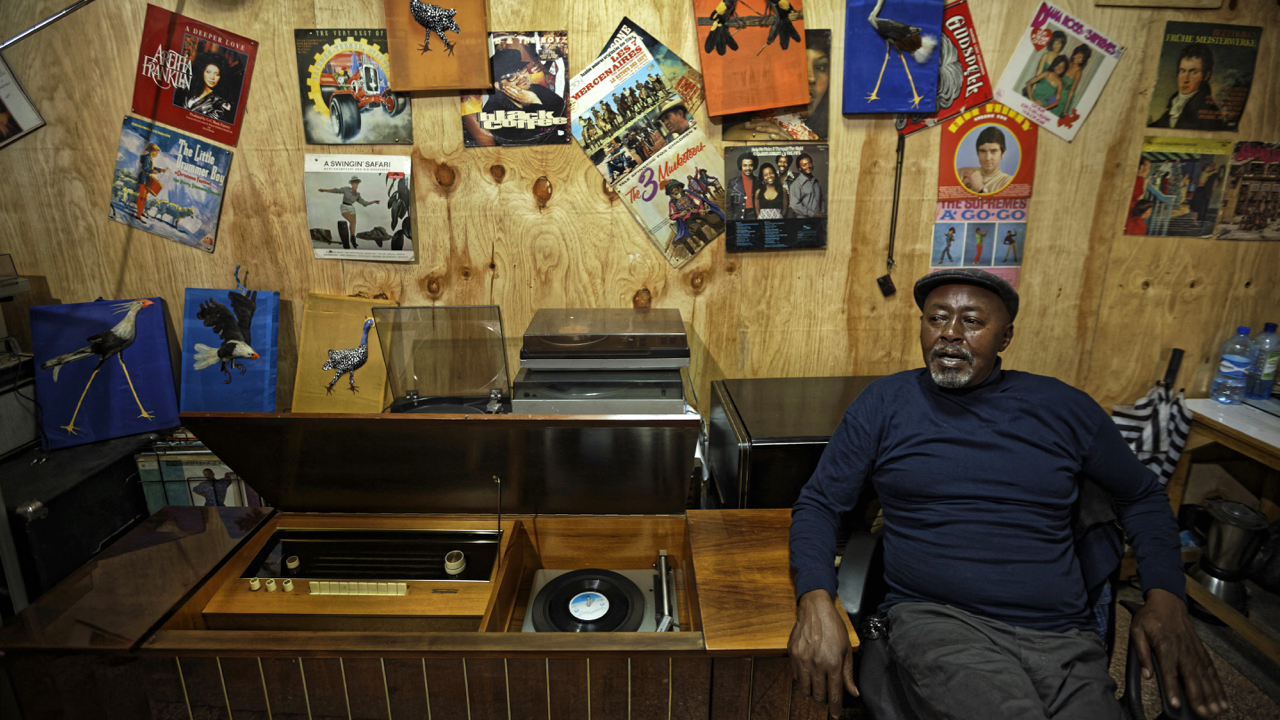 """In this photo taken Thursday, March 1, 2018, James """"Jimmy"""" Rugami recounts his story inside his vinyl records stall in Kenyatta Market in Nairobi, Kenya. Tucked into a busy market in Kenya's capital is """"Real Vinyl Guru"""", arguably the last record store still in operation in the country and which now enjoys the growing interest of music lovers who want to look beyond sleek digital offerings and return to the pleasure of browsing for a classic find. (AP Photo/Ben Curtis)"""