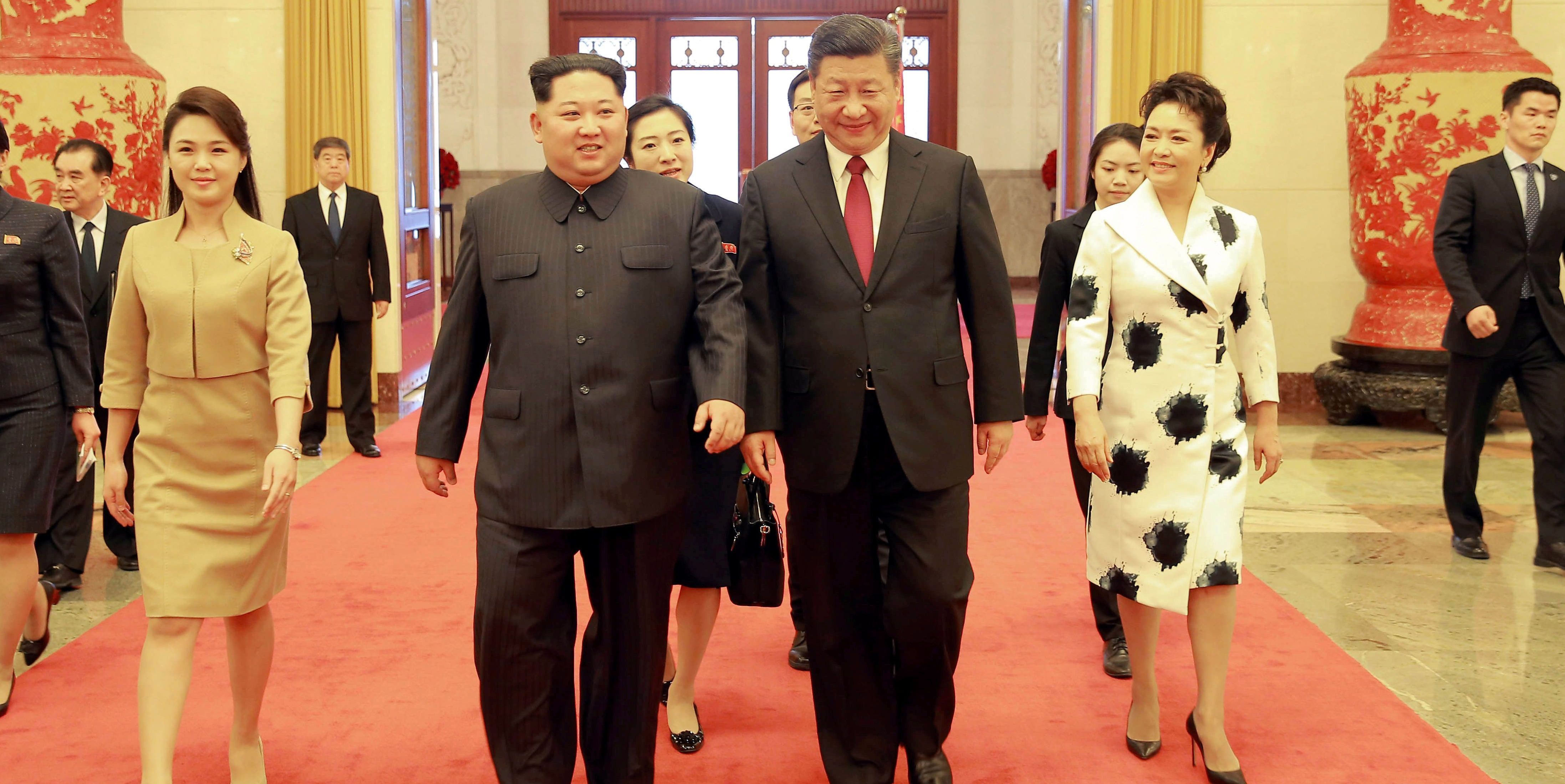 North Korean leader Kim Jong Un and wife Ri Sol Ju, and Chinese President Xi Jinping and wife Peng walk together
