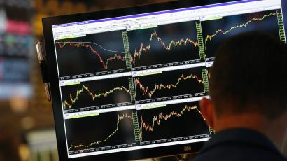 A screen displays stock charts while a trader works
