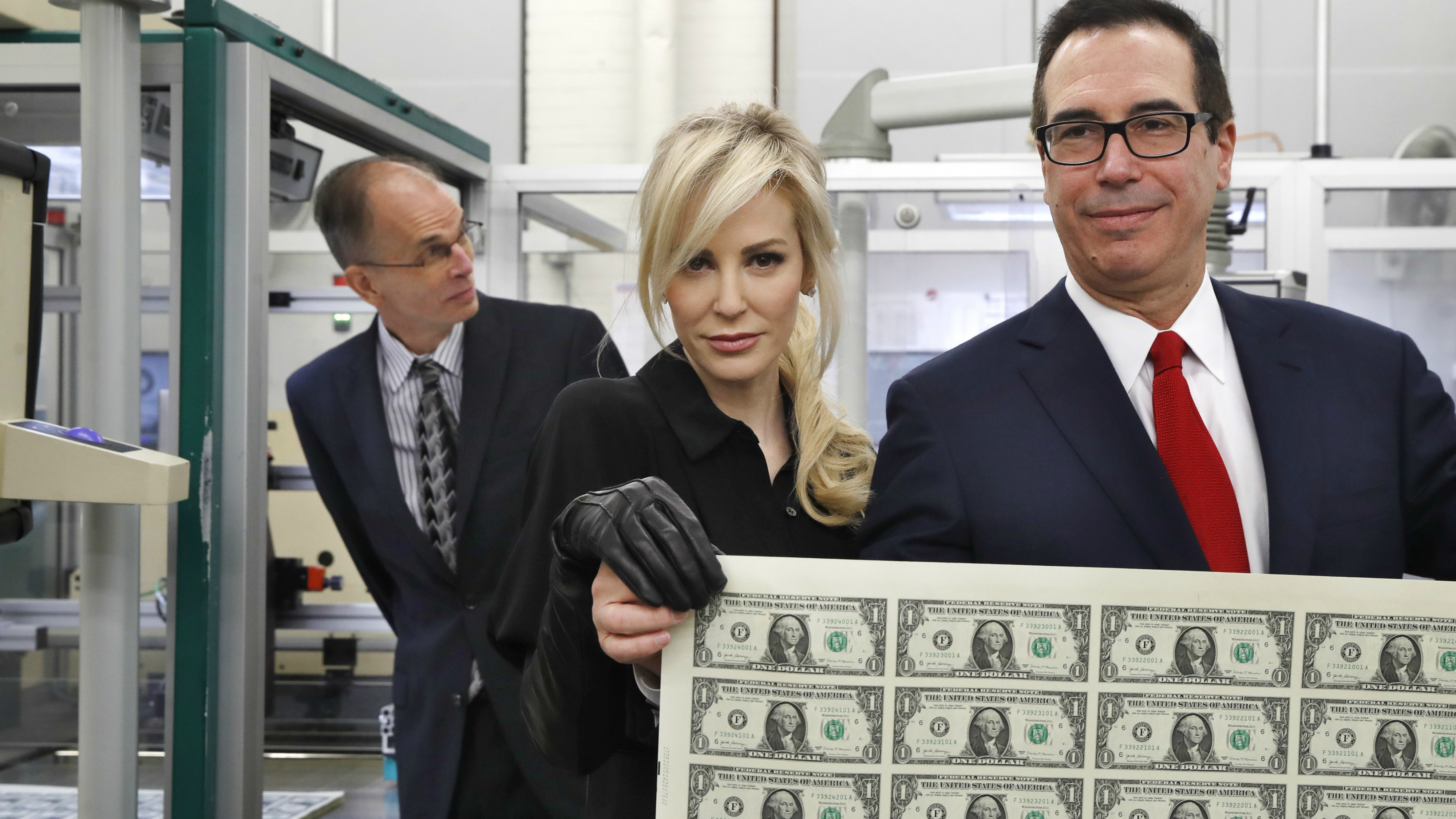 Treasury Secretary Steven Mnuchin, right, and his wife Louise Linton, hold up a sheet of new $1 bills.