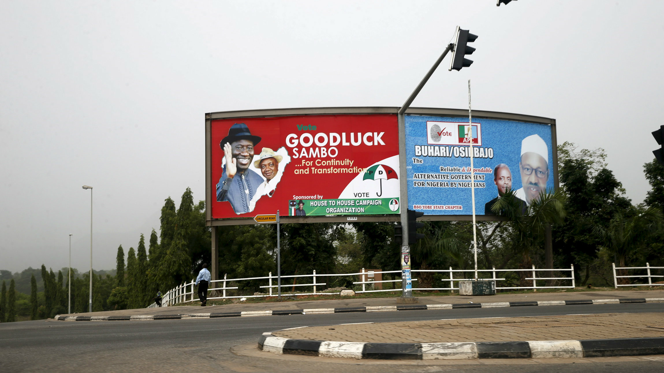 A billboard advertising for the re-election President Goodluck Jonathan is seen standing next to another one campaigning for President-elect Muhammadu Buhari in the capital Abuja April 1, 2015. As Muhammadu Buhari closed in on Nigeria's presidency, an aide to election commission chairman Attahiru Jega sent a text message to an independent voting monitor, warning of an imminent threat to the electoral process. The aide had unearthed a plot by supporters of President Goodluck Jonathan to disrupt the public announcement of the national election results and kidnap Jega in a bid to wreck the count, according to pro-democracy advocates and a Nigeria-based diplomat. Picture taken April 1, 2015.