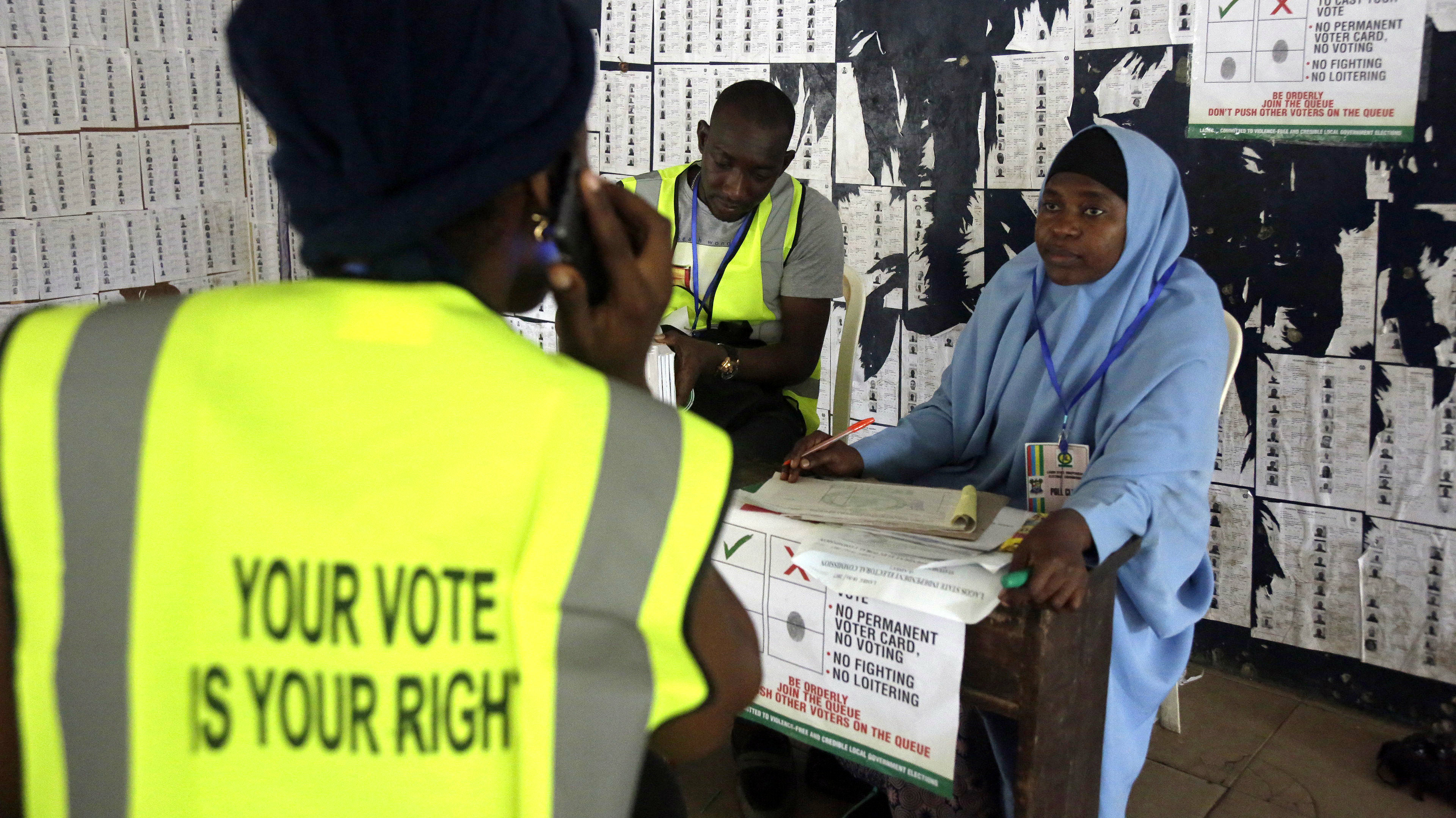 Election officials wait for voters during a local government election in Lagos, Nigeria, Saturday, July 22, 2017. Voters cast ballots Saturday for council members and leaders of local government areas. Voting mostly went smoothly, although some polling stations saw ballots arrive hours late due to a downpour