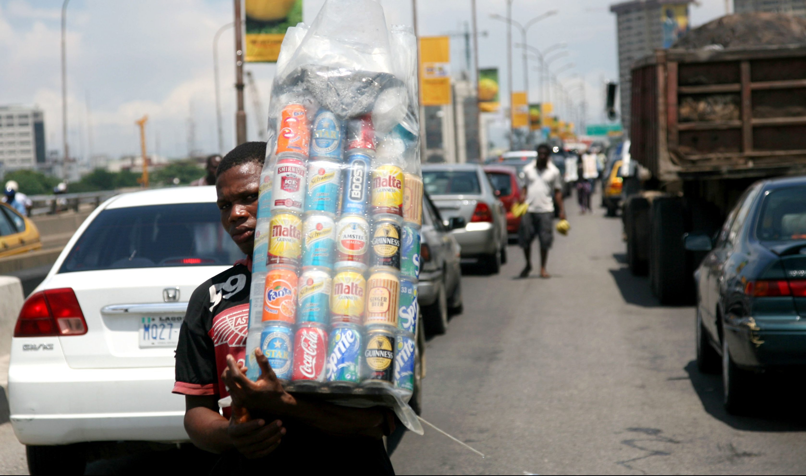 A man sells drinks in between traffic in Nigeria's commercial capital Lagos