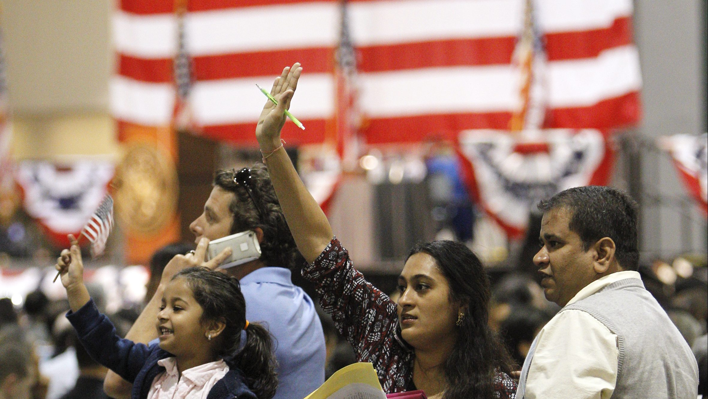 Sarika Vakil (C), her husband Tejas Vakil (R), originally from Mumbai, India and their four-year-old daughter Tashu (L) wave to family members who were in attendance to support them, before Sarika and Tejas, together with thousands of immigrants, take the oath of allegiance to the U.S. Constitution, as the final step to becoming a naturalized U.S. citizen, during naturalization ceremonies in Los Angeles, March 31, 2010. Tashu is a U.S. citizen as she was born in the U.S. REUTERS/Danny Moloshok (UNITED STATES - Tags: SOCIETY POLITICS) - GM1E6410I1901