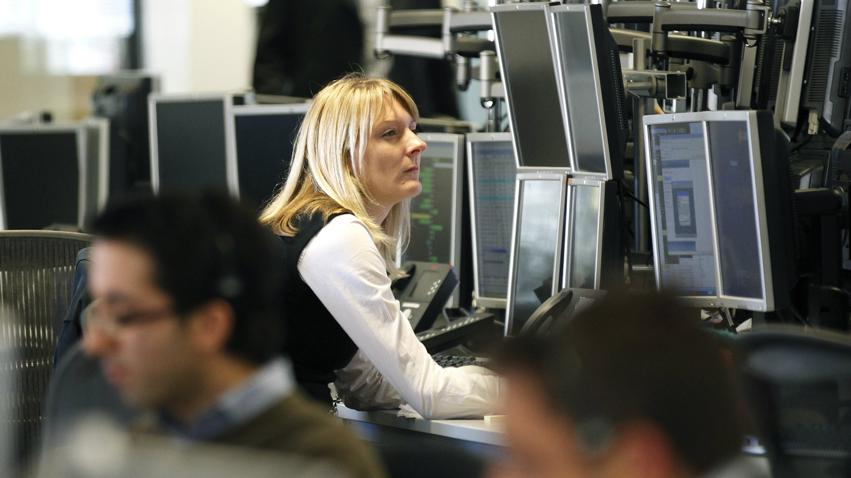 A woman monitors her screens at a dealing floor in London