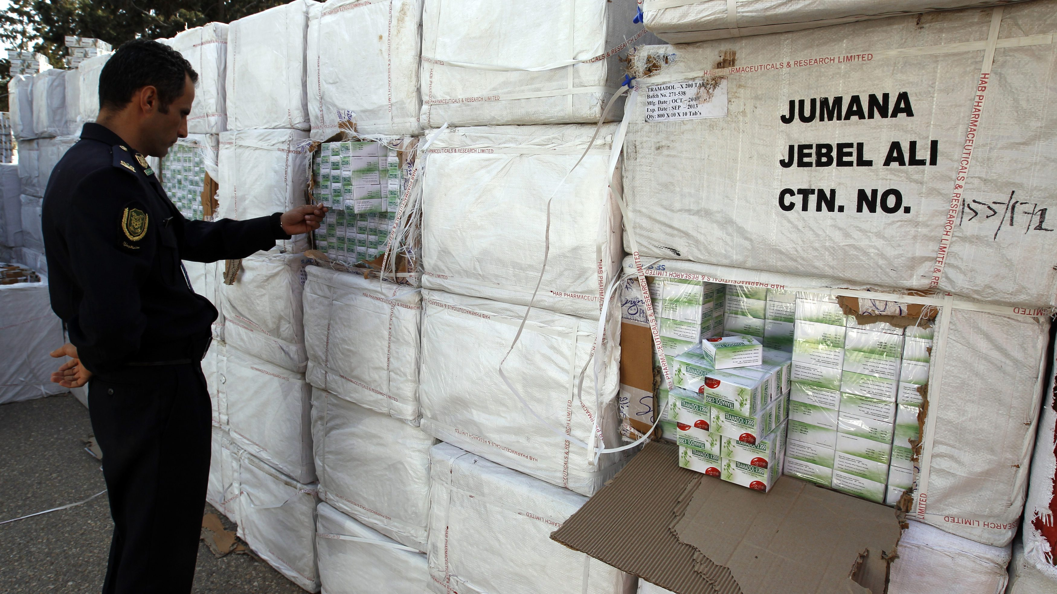 A Libyan police officer views a haul of prescription drug Tramadol seized from a shipping container in Tripoli