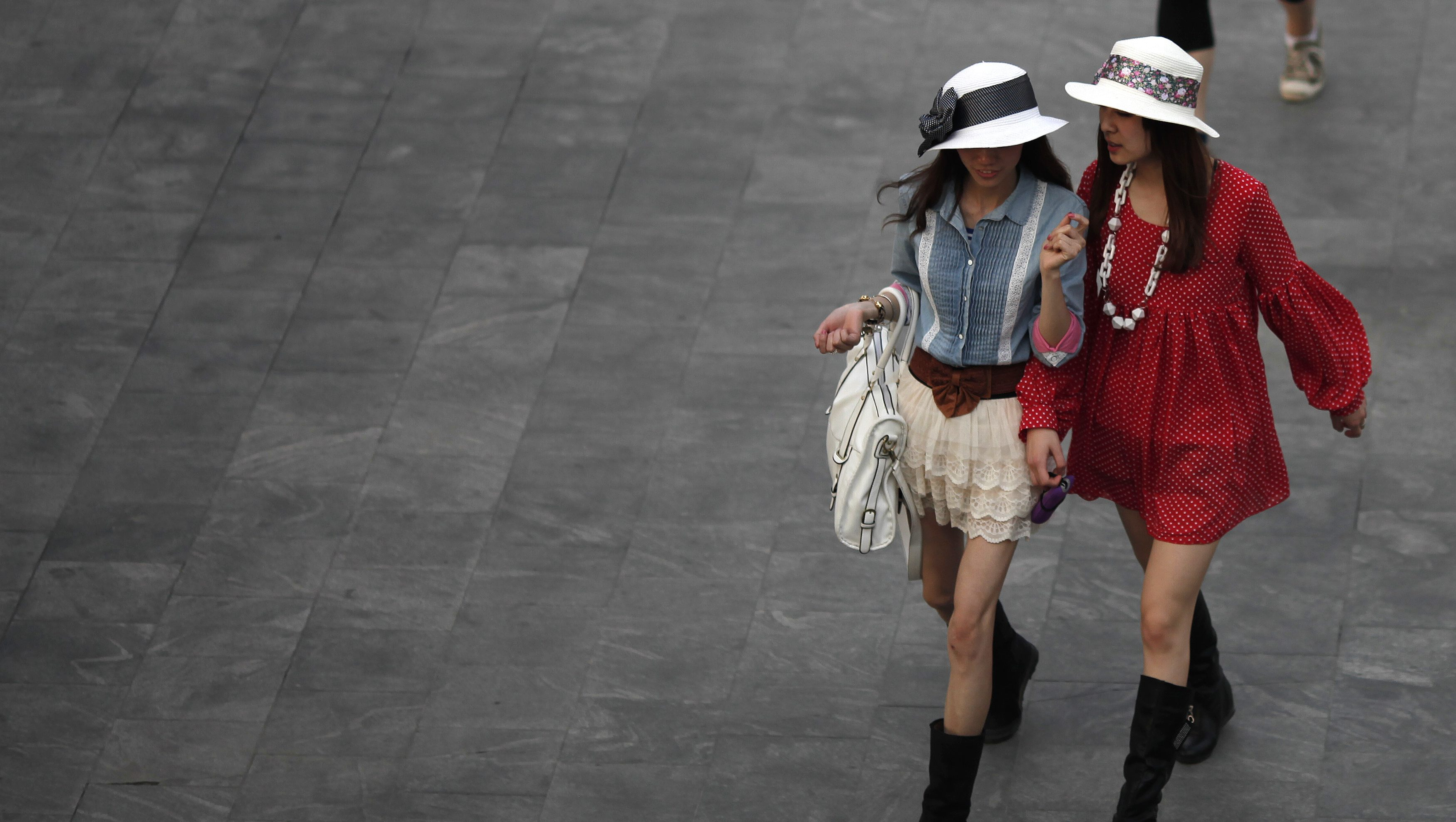 Women walk in the financial area of Pudong in Shanghai April 26, 2011.