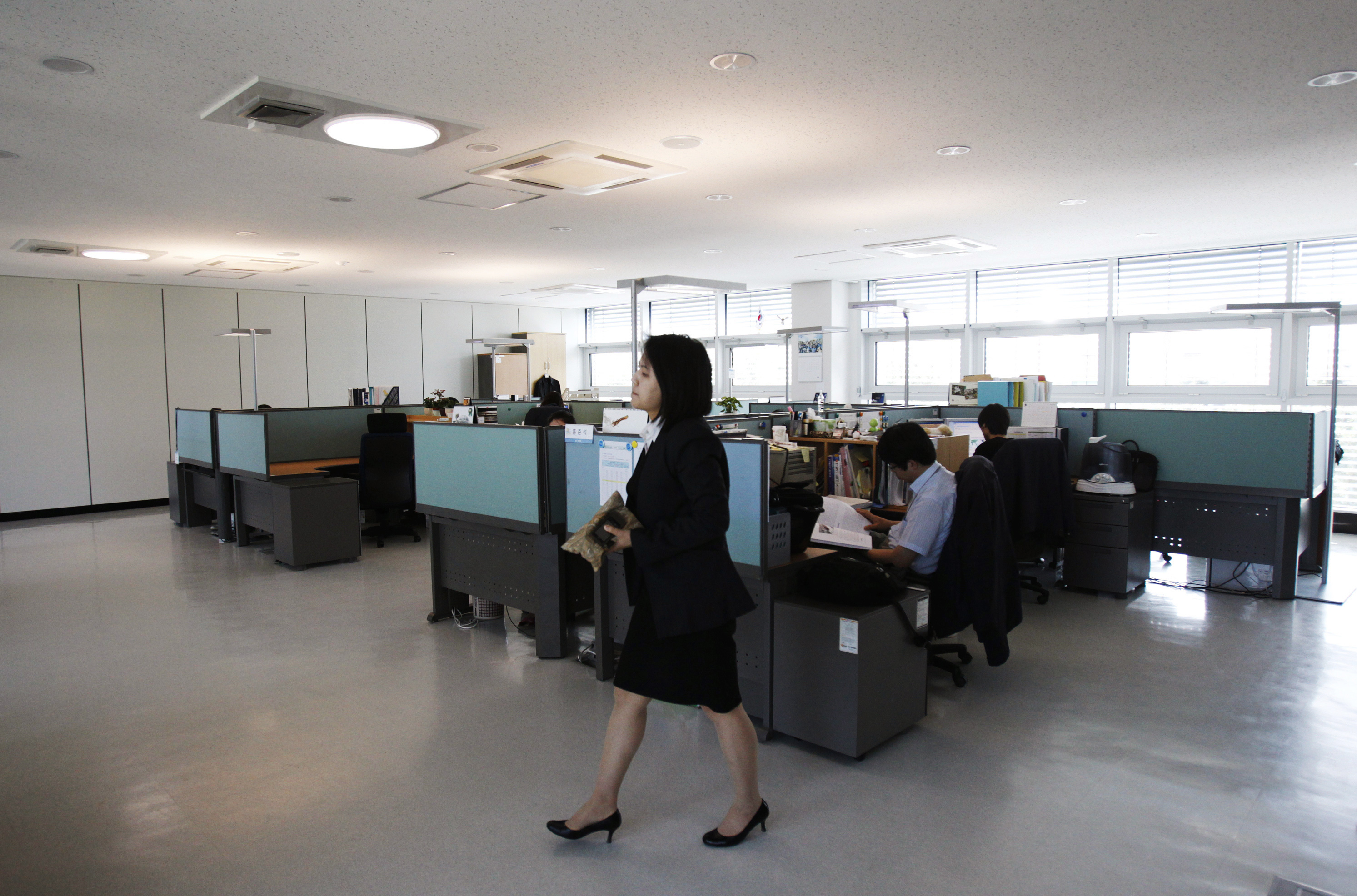 Officials of the National Institute of Environmental Research (NIER) work in the office at its zero carbon building in Incheon, west of Seoul, May 16, 2011. South Korea has opened what it says is the ultimate eco-friendly business centre, a construction that emits zero carbon and uses only renewable energy, in a project to underline the government's commitment to reduce greenhouse gases. The 2,500 square-metre building, which houses a climate change research centre at Incheon near the capital Seoul, was opened in April by the environment ministry at a cost of around $8 million. Picture taken May 16. To match Reuters Life! KOREA-GREEN/ REUTERS/Truth Leem (SOUTH KOREA - Tags: ENVIRONMENT SOCIETY BUSINESS CONSTRUCTION ENERGY) - GM1E75K1K5Q01