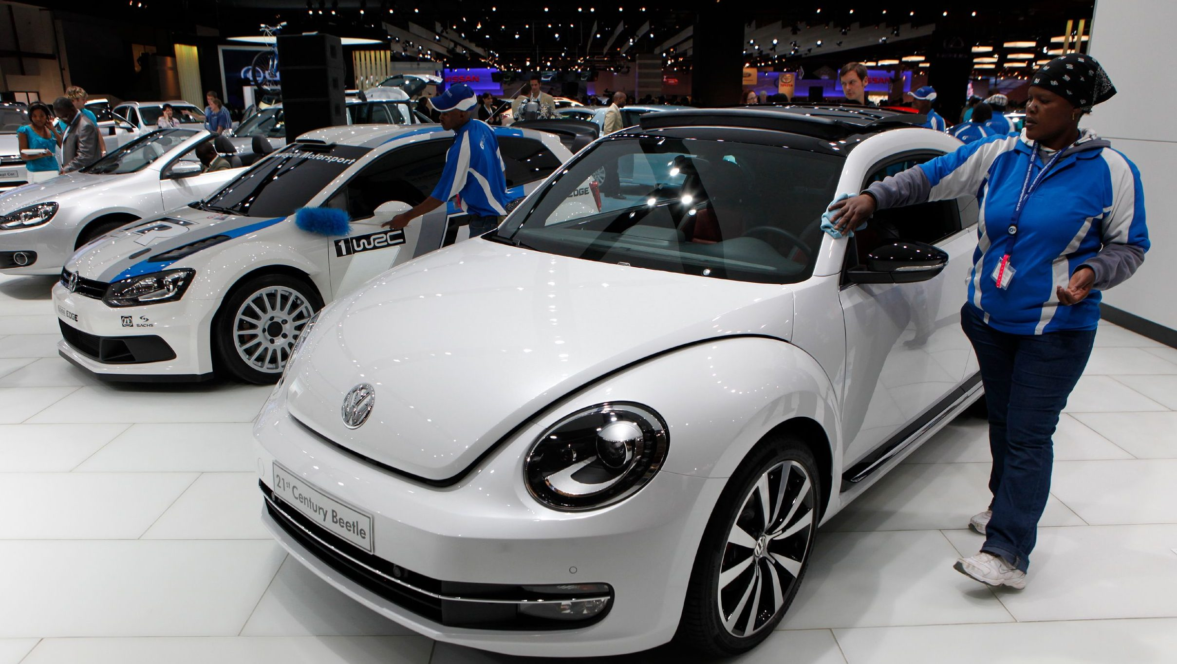 A worker cleans a 2012 Volkswagen 21st Century Beetle during the Johannesburg International Motor Show at Nasrec in Johannesburg October 6, 2011.
