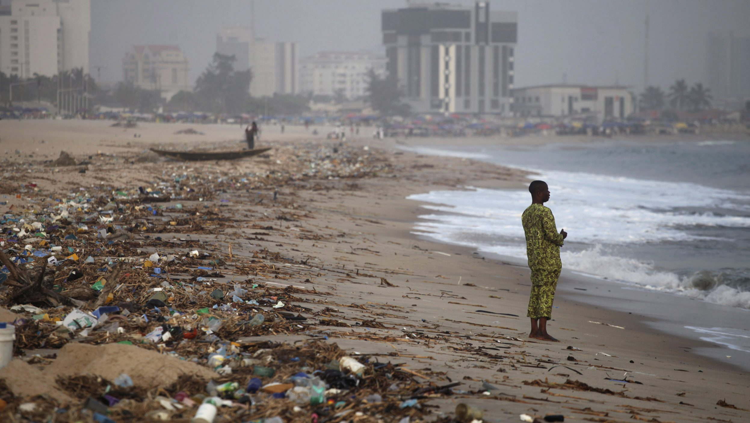 A man stands on the shore of Bar Beach, awash with rubbish and waste, in Lagos