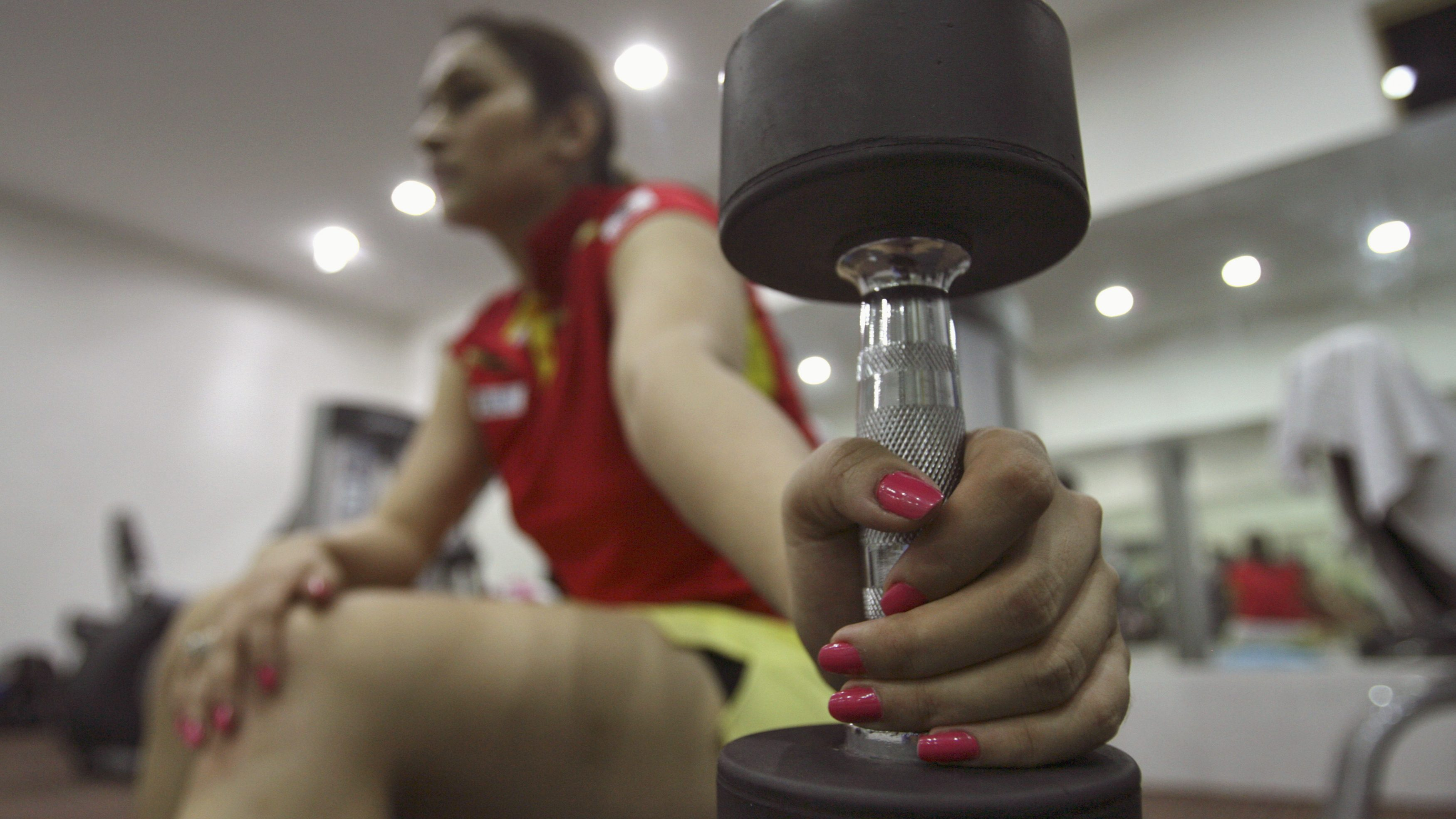 India's badminton player Jwala Gutta holds a dumbbell while taking a break during her exercise at a gym before a practice session in preparation for the London Olympics, in the southern Indian city of Hyderabad July 12, 2012. Gutta thinks it may take India 100 years to emulate China's sporting success but the badminton doubles specialist hopes to bring her country a step closer to that goal by earning a medal at the London Olympics. To match Interview OLY-BADM-INDIA-GUTTA-ADV11/ Picture taken July 12, 2012. REUTERS/Krishnendu Halder (INDIA - Tags: SPORT BADMINTON OLYMPICS) - GM1E87G1EYA01