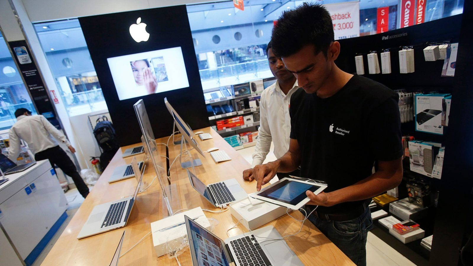 A salesperson unpacks an Apple iPad Mini to test it for a customer in the Apple specialty section of a Croma retail store in Mumbai February 22, 2013. The store offers Apple products including iPhones and iPads on instalment plans. More than four years after it started selling iPhones in India, Apple Inc is now aggressively pushing the iconic device through instalment payment plans that make it more affordable, a new distribution model and heavy marketing blitz. The result: iPhone shipments to India between October and December of 2012 nearly tripled to 250,000 units from 90,000 in the previous quarter, according to an estimate by Jessica Kwee, a Singapore-based analyst at consultancy Canalys. Picture taken February 22, 2013. REUTERS/Vivek Prakash (INDIA - Tags: BUSINESS SCIENCE TECHNOLOGY) - GM1E92O1UB001