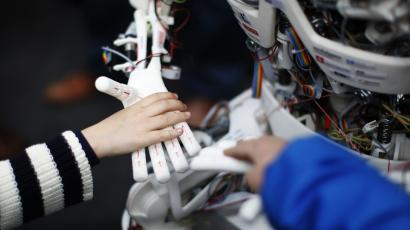 Children touch the hands of the humanoid robot Roboy at the exhibition Robots on Tour in Zurich