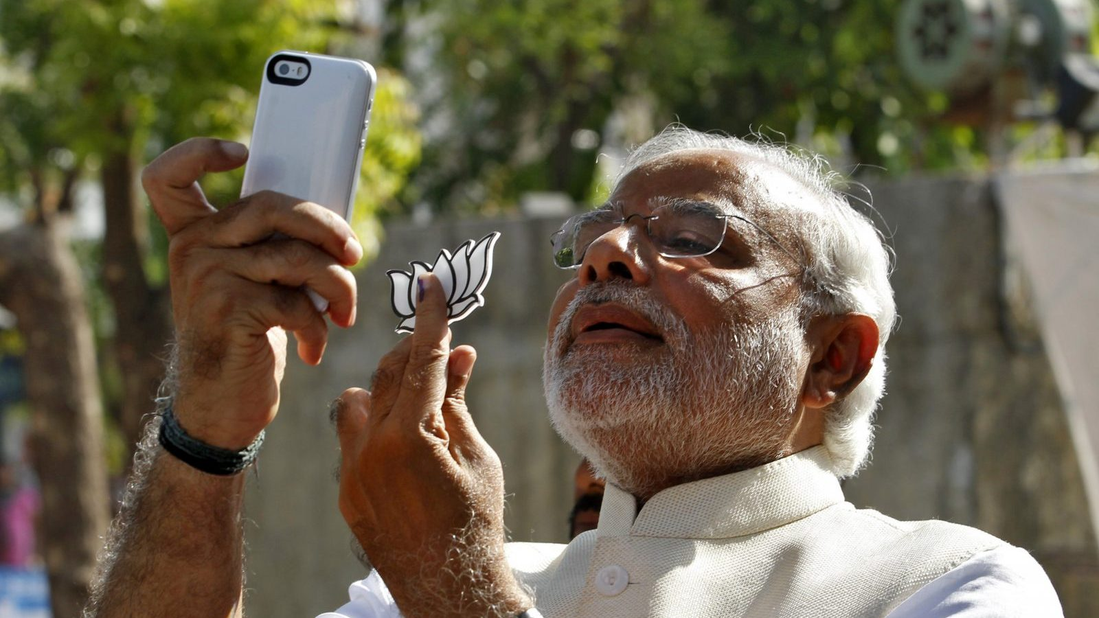 """Hindu nationalist Narendra Modi, the prime ministerial candidate for India's main opposition Bharatiya Janata Party (BJP), takes a """"selfie"""" with a mobile phone after casting his vote at a polling station during the seventh phase of India's general election in the western Indian city of Ahmedabad April 30, 2014. Around 815 million people have registered to vote in the world's biggest election - a number exceeding the population of Europe and a world record - and results of the mammoth exercise, which concludes on May 12, are due on May 16. REUTERS/Amit Dave (INDIA - Tags: POLITICS ELECTIONS TPX IMAGES OF THE DAY) - GM1EA4U11JO01"""