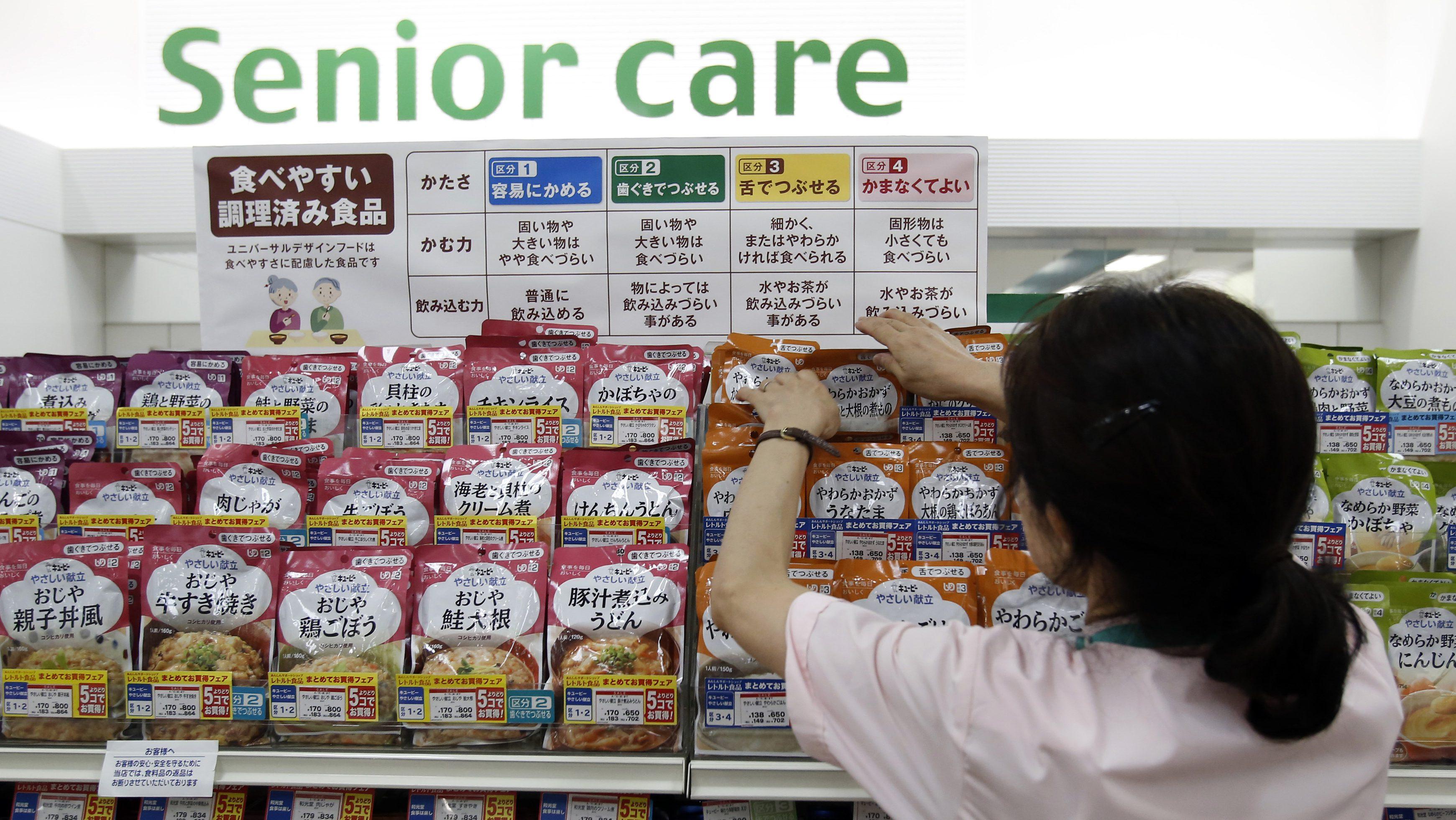 A staff arranges Kewpie Corp's nursing care food packages on a display shelf in Tokyo in 2014.