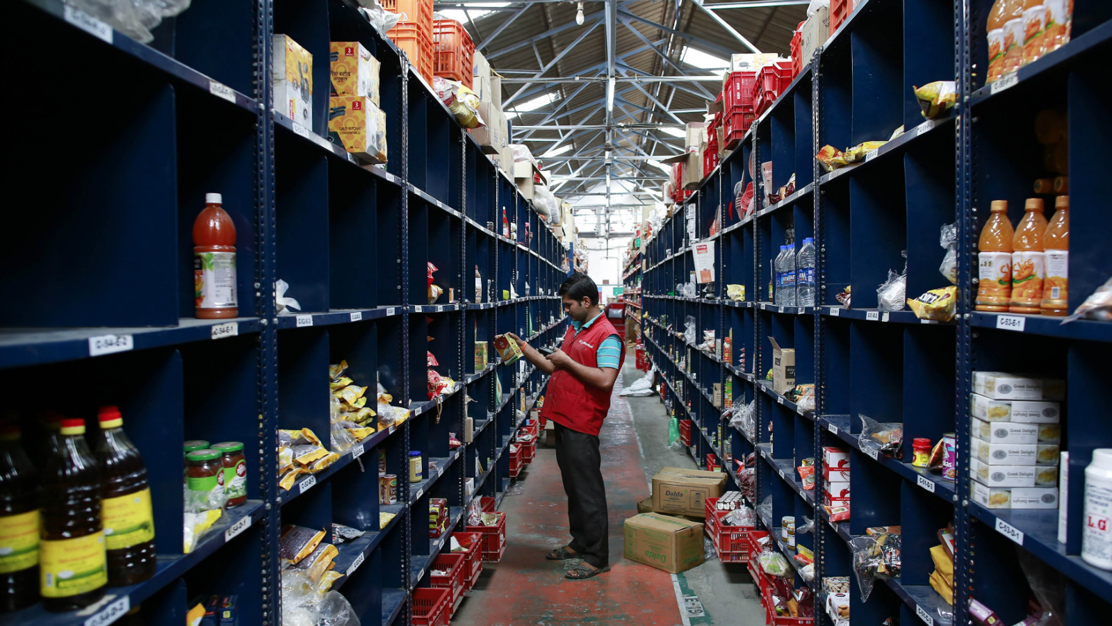 An employee scans a package for an order at a Big Basket warehouse on the outskirts of Mumbai November 4, 2014. Put off by snarled city traffic and a shortage of parking, more Indians are shopping for groceries online, helping e-tailers like Bigbasket.com and Localbanya.com turn in profits while supermarkets are struggling. Picture taken November 4.