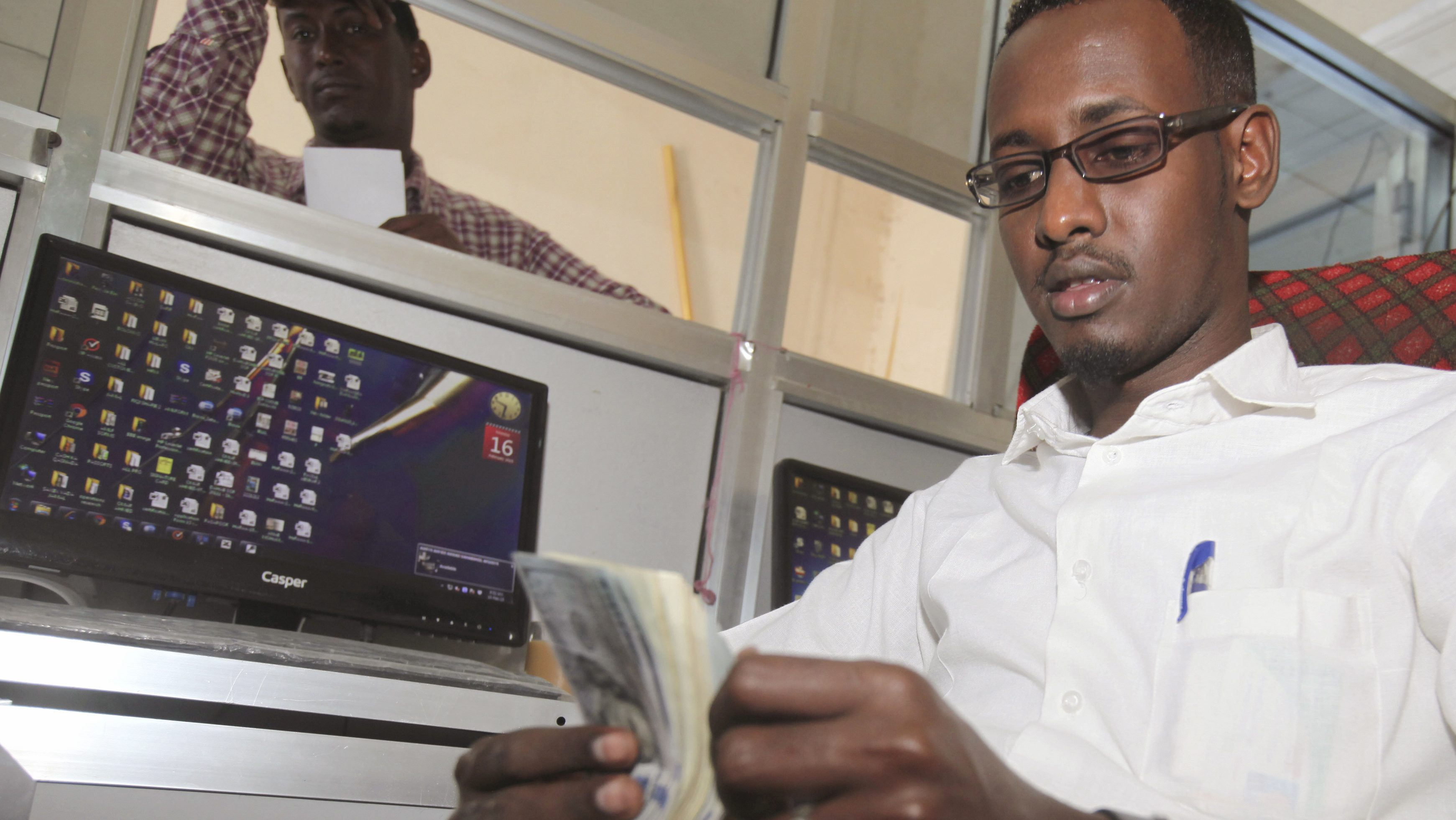 A worker at the Dahabshill money transfer office counts U.S. notes in capital Mogadishu