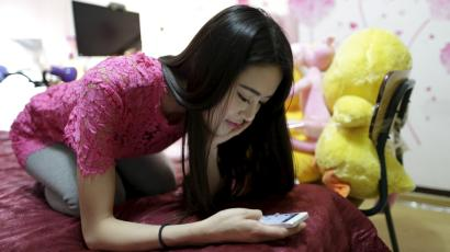 Online hostess Xianggong checks her mobile phone as she sits on her bed after a live broadcast in Beijing, February 10, 2015. In China's online hostessing world, men find virtual company and the women can find riches. Xianggong is one of more than 10,000 hostesses on the internet site bobo.com, a live broadcasting web platform where anyone can record themselves singing, playing piano, dancing or just chatting.