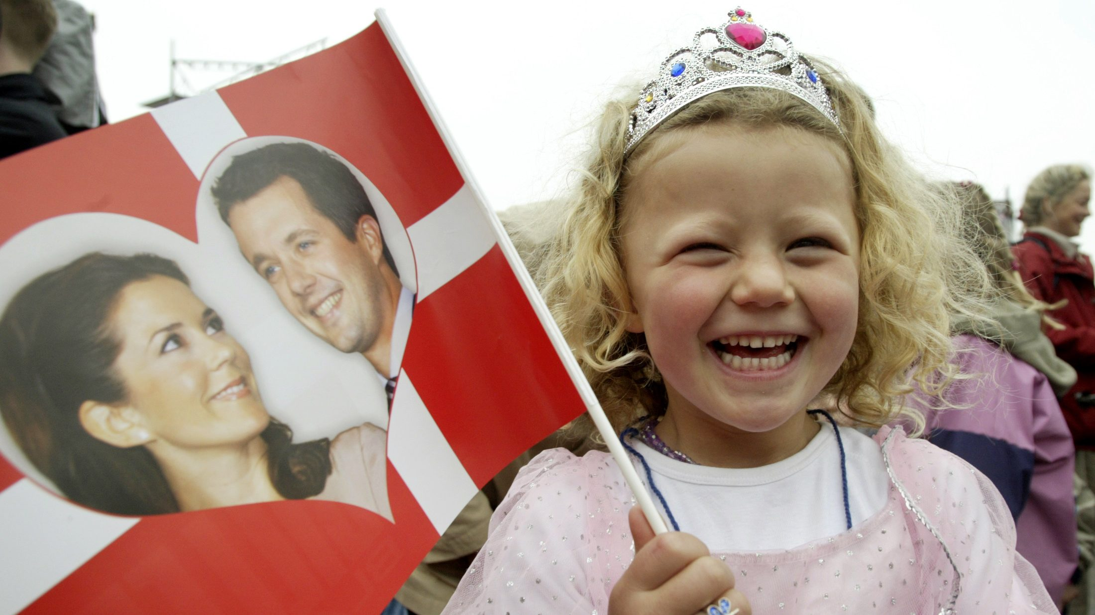A GIRL DRESSED AS A PRINCESS WAVES WITH A FLAG SHOWING THE ROYAL COUPLE DANISH CROWN PRINCE FREDIK AND HIS AUSTRALIAN FIANCE MARY DONALDSON IN COPENHAGEN.  A girl dressed as a princess waves a flag showing Danish Crown Prince Frederik and his Australian fiance Mary Donaldson outside the Copenhagen cityhall, May 12. Frederik, the 35-year-old heir to the throne of one of Europe's oldest monarchies will marry 32-year-old lawyer Mary Donaldson on Friday May 14, 2004, the first Australian to marry into a European royal house that still has its throne.