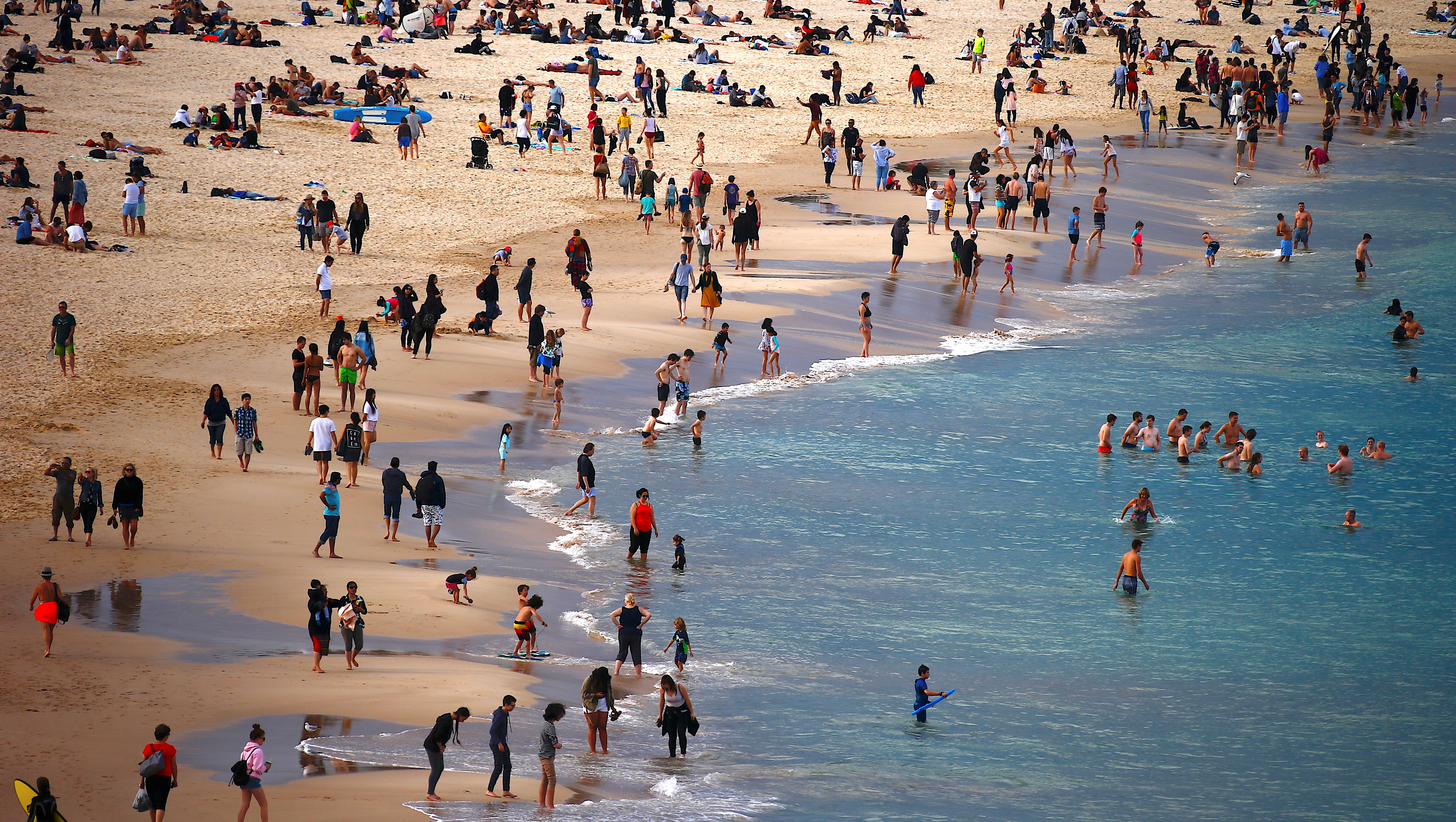 Beachgoers swim and stand on the edge of the water at Sydney's Bondi Beach on a winter day in Australia