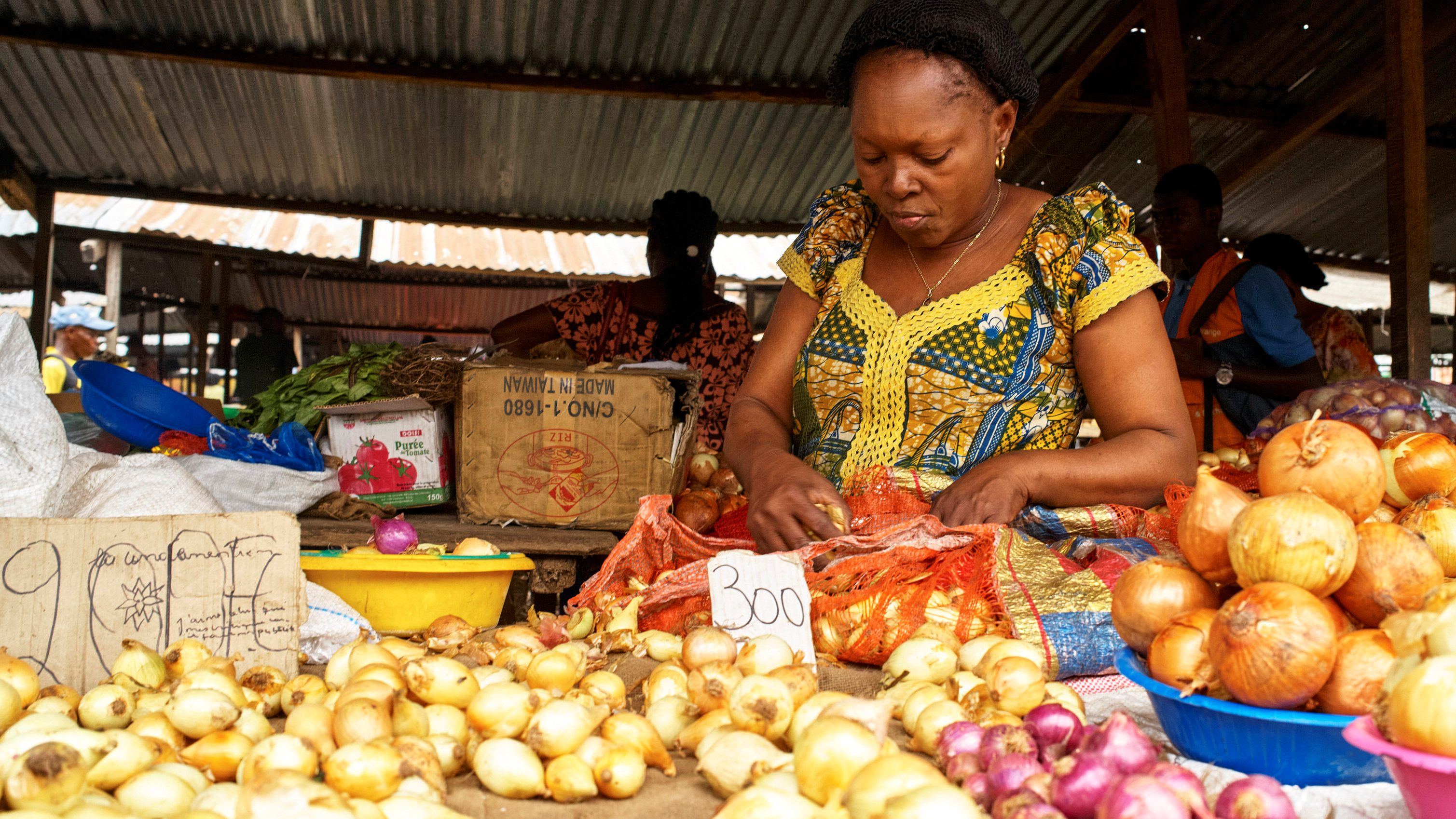 A vendor arranges onions and vegetables at her grocery stall at the Sigida Market, within Kinshasa Municipality, in Kinshasa