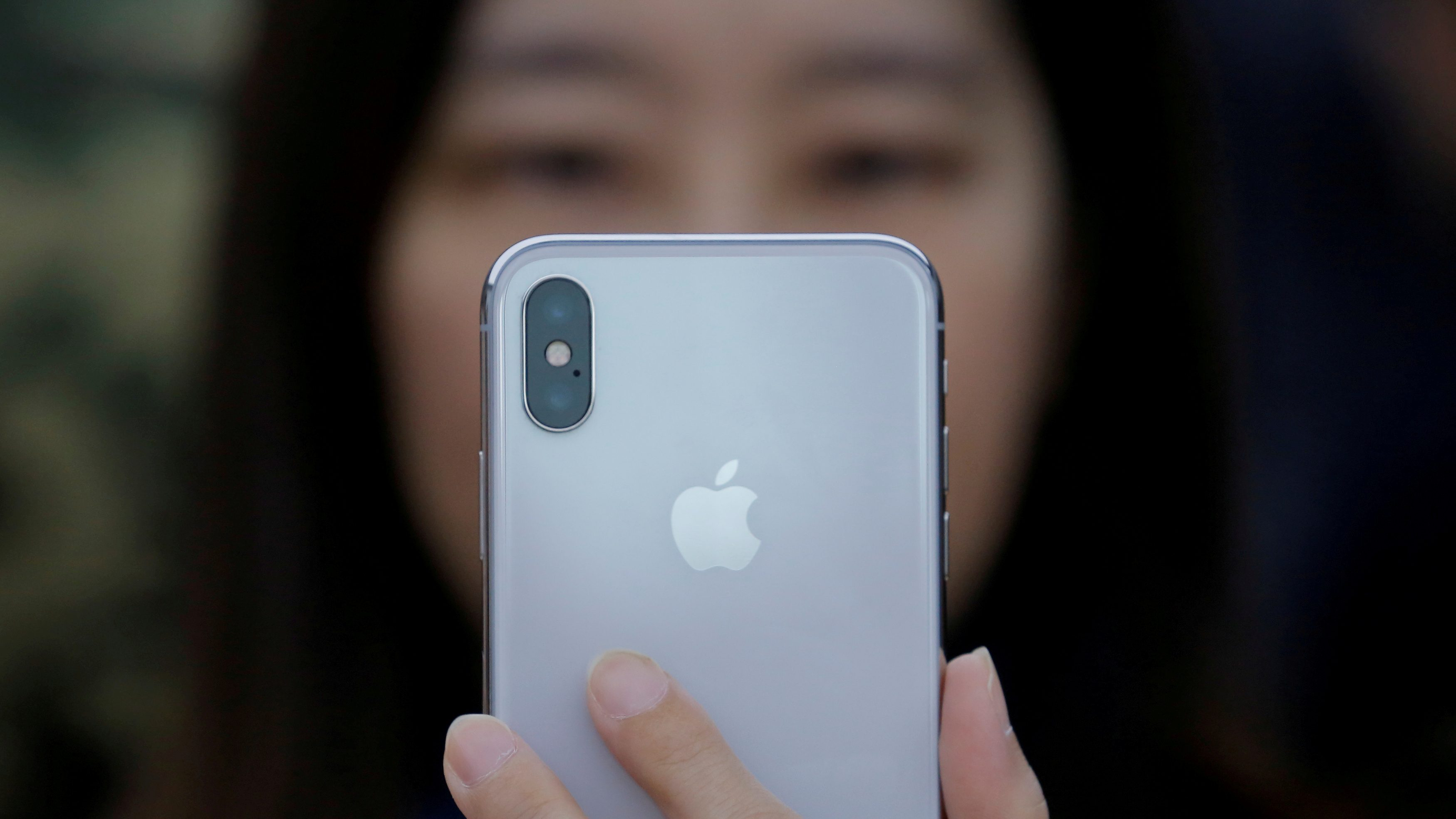 A attendee uses a new iPhone X during a presentation for the media in Beijing, China October 31, 2017.
