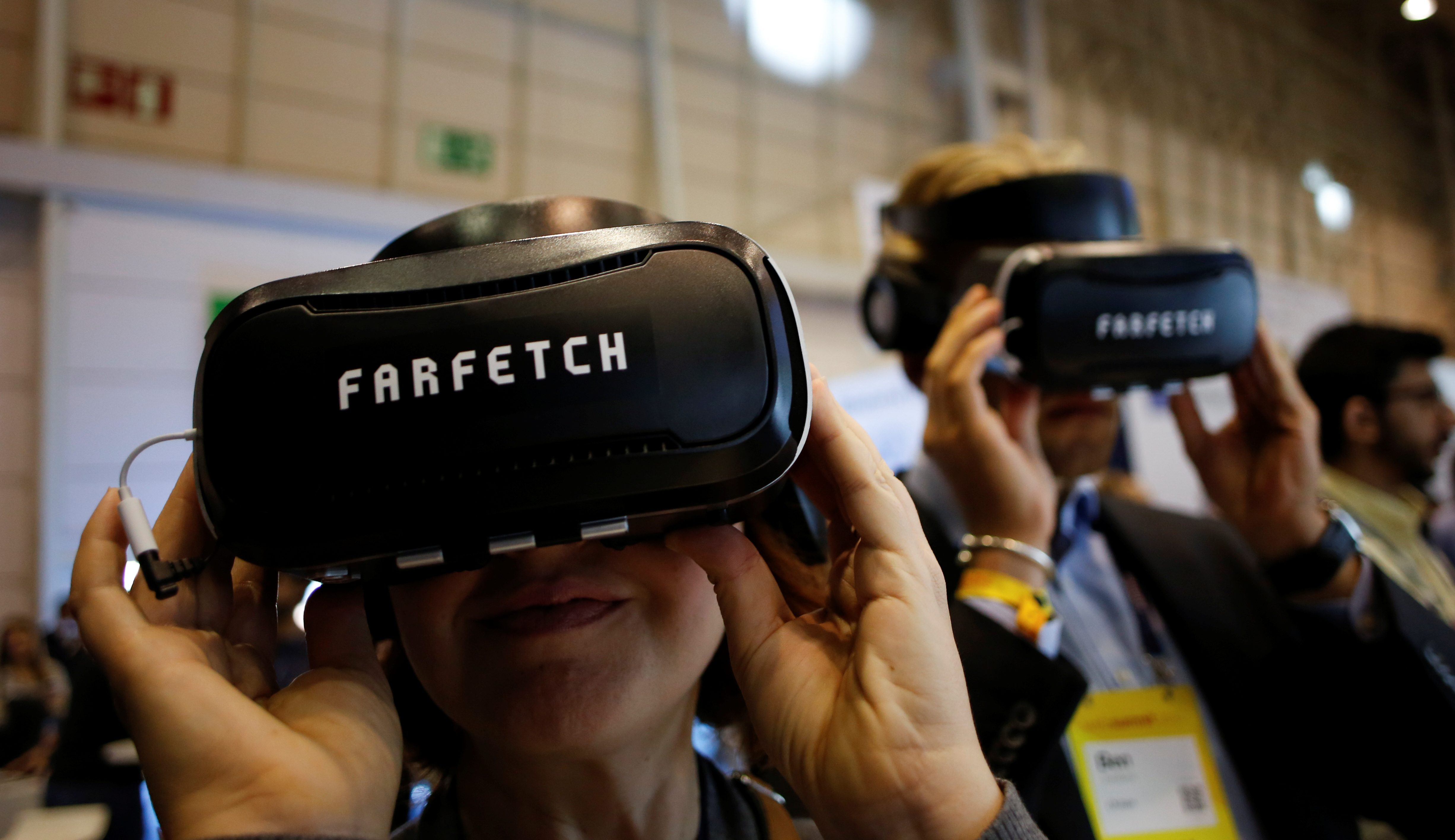 Visitors wear virtual reality glasses at the Farfetch stand during the Web Summit, Europe's biggest tech conference, in Lisbon, Portugal, November 8, 2017. REUTERS/Pedro Nunes - RC12C58A7850