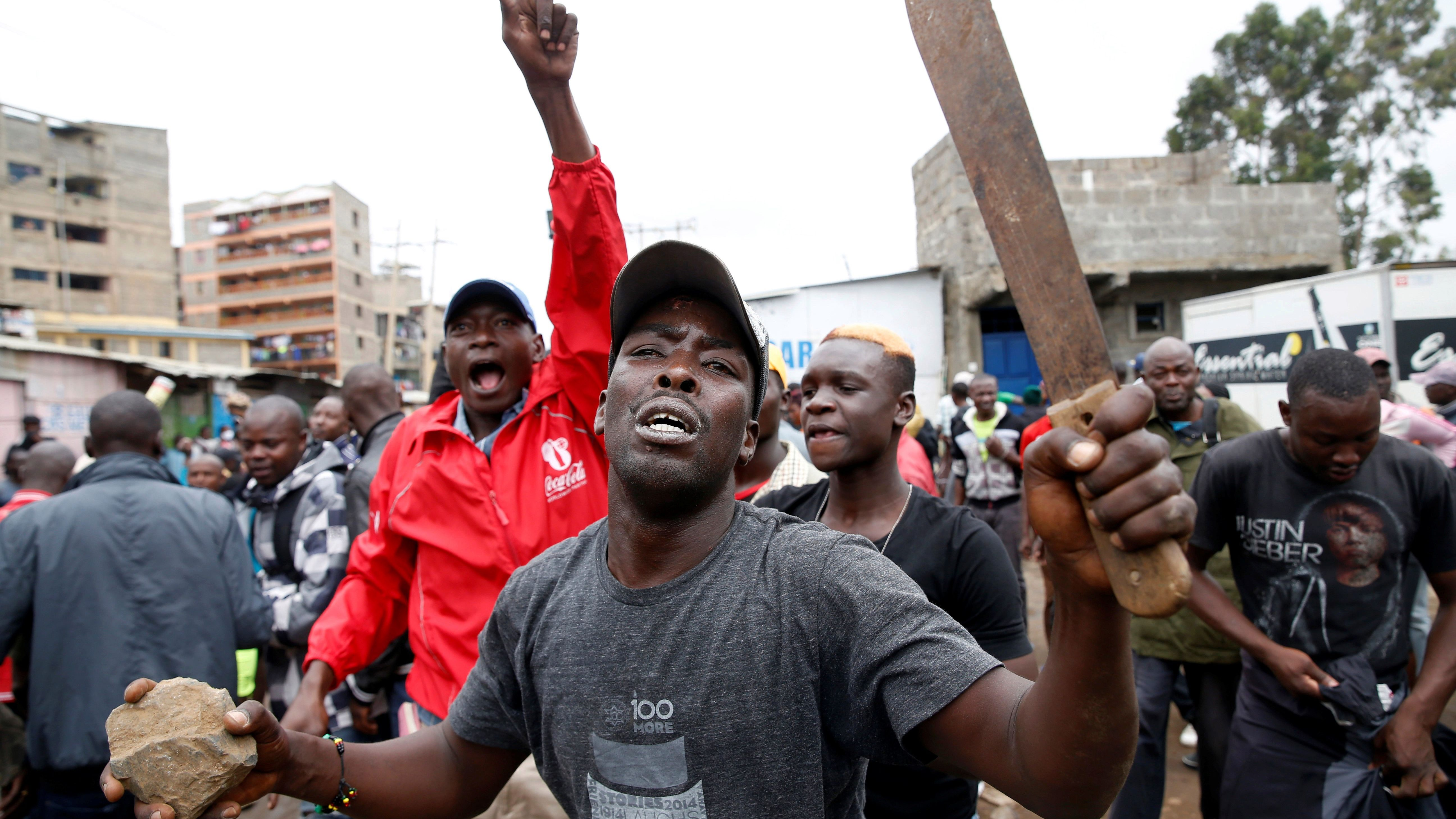 Supporters of of Kenyan opposition National Super Alliance (NASA) coalition react during clashes with anti-riot police in the Baba Dogo neighborhood of Nairobi