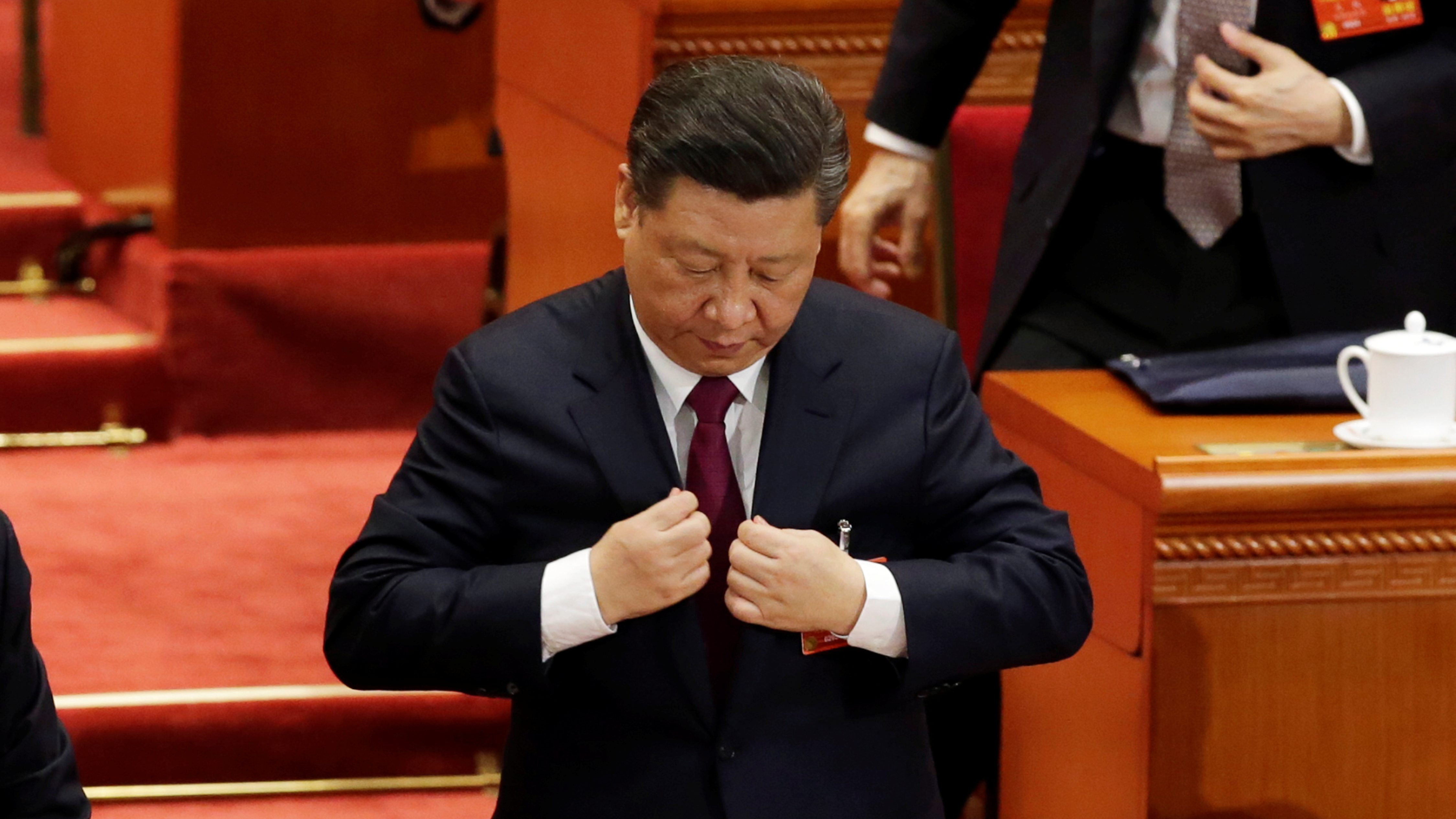 Chinese President Xi Jinping adjusts his attire at the end of the opening session of the National People's Congress (NPC) at the Great Hall of the People in Beijing, China March 5, 2018.