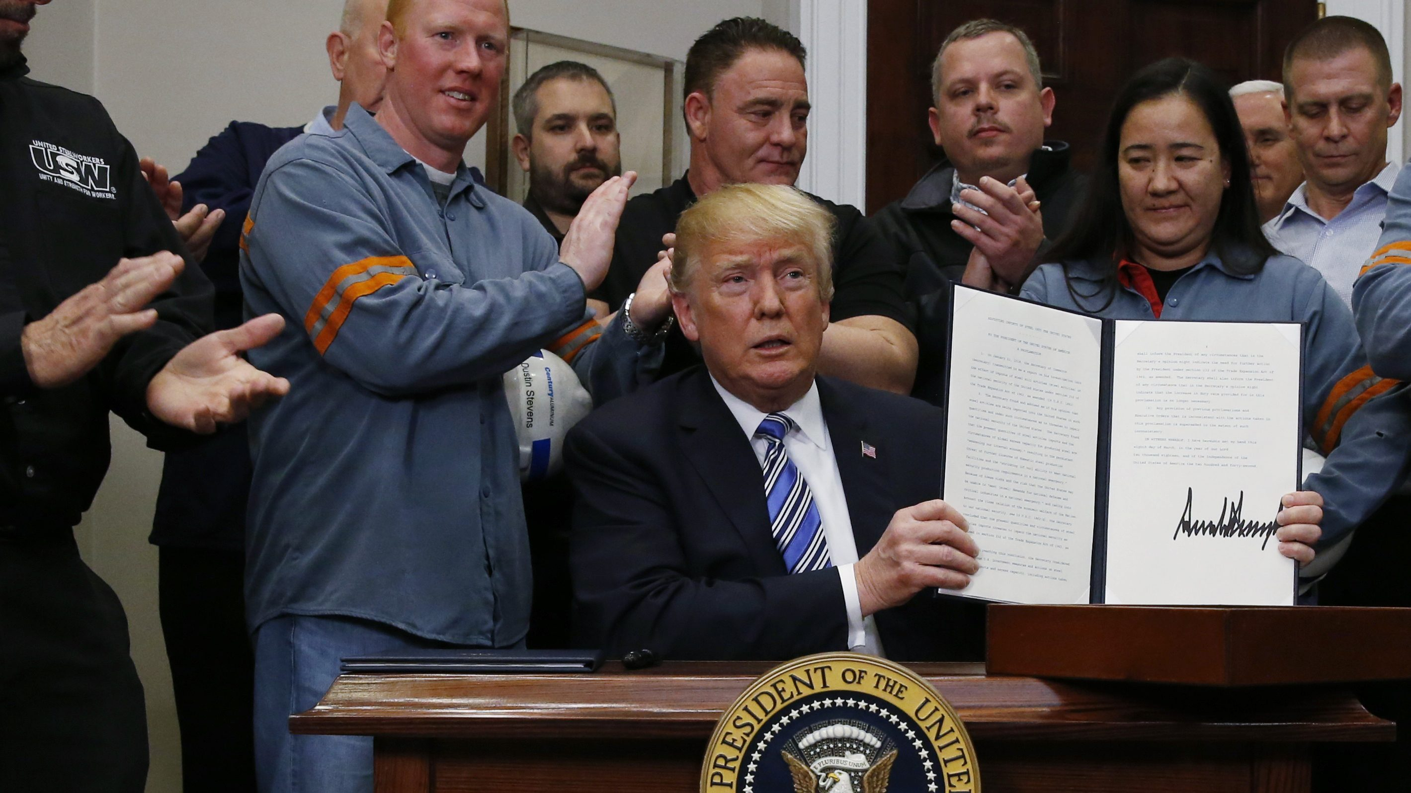 U.S. President Donald Trump holds up a proclamation during a White House ceremony to establish tariffs on imports of steel and aluminum at the White House in Washington, U.S., March 8, 2018. REUTERS/Leah Millis - HP1EE381MRMAS
