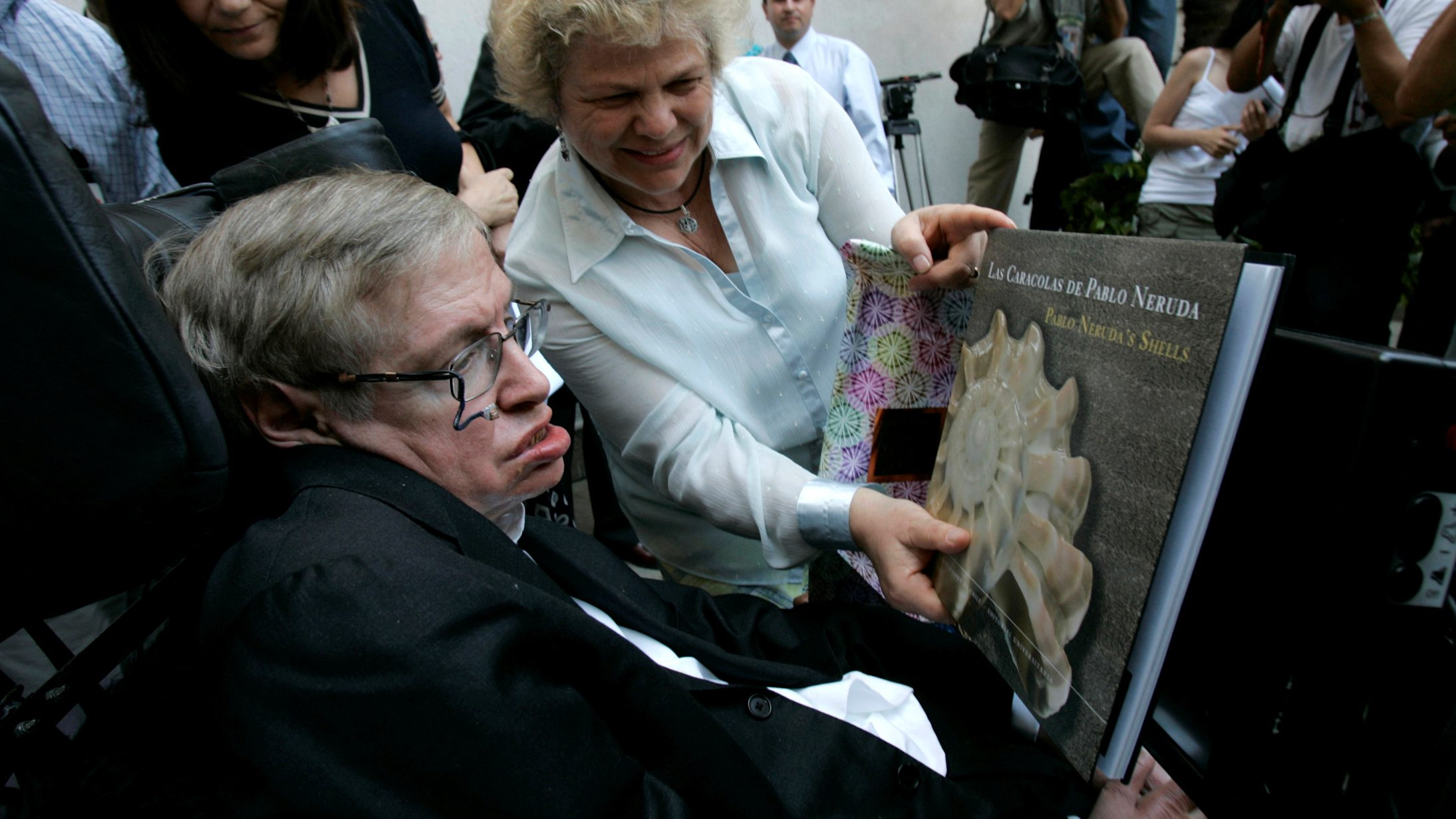 FILE PHOTO: British physicist Stephen Hawking looks at a book of Chile's Nobel Laureate Pablo Neruda after a meeting with Chile's President Michelle Bachelet (unseen) at the Presidential Palace in Santiago January 17, 2008.  REUTERS/Victor Ruiz Caballero/File Photo - RC199AE233F0